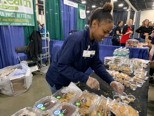 Bria Glenn sets out samples from at the Better Health Market & Cafe booth at the Michigan VegFest on Sunday, April 28, 2019 at the Suburban Collection Showplace in Novi.