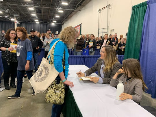 Actress Alicia Silverstone sits with her son Bear as she signs a book for Robin Orr, of Romulus, 49, at the Michigan VegFest on Sunday, April 28, 2019 at the Suburban Collection Showplace in Novi.