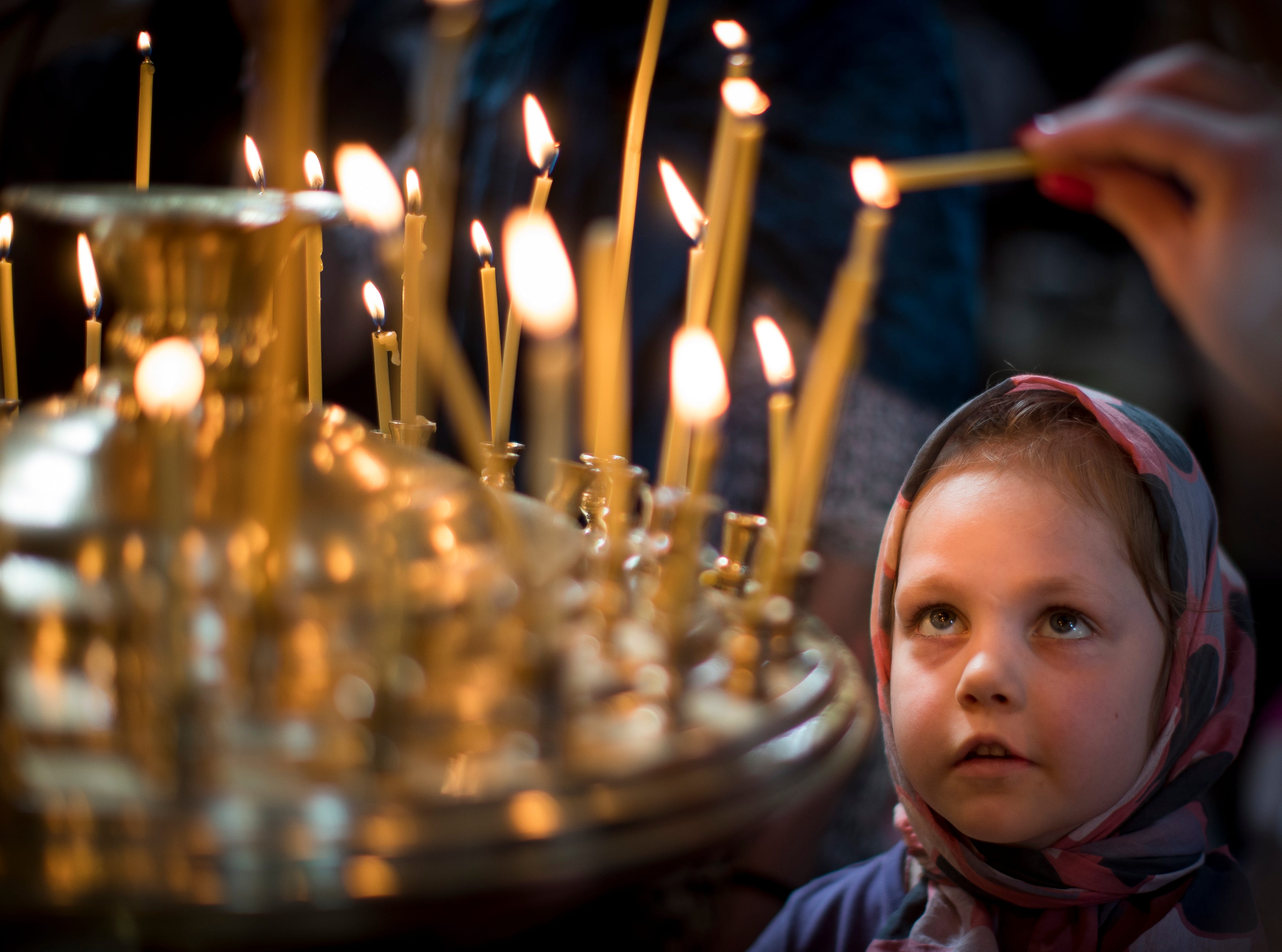 Worshippers light candles during the Easter service at the Orthodox Church of the Holy Spirit in Vilnius, Lithuania, Saturday, April 27, 2018. Orthodox Christians around the world celebrate Easter on Sunday, April 28.