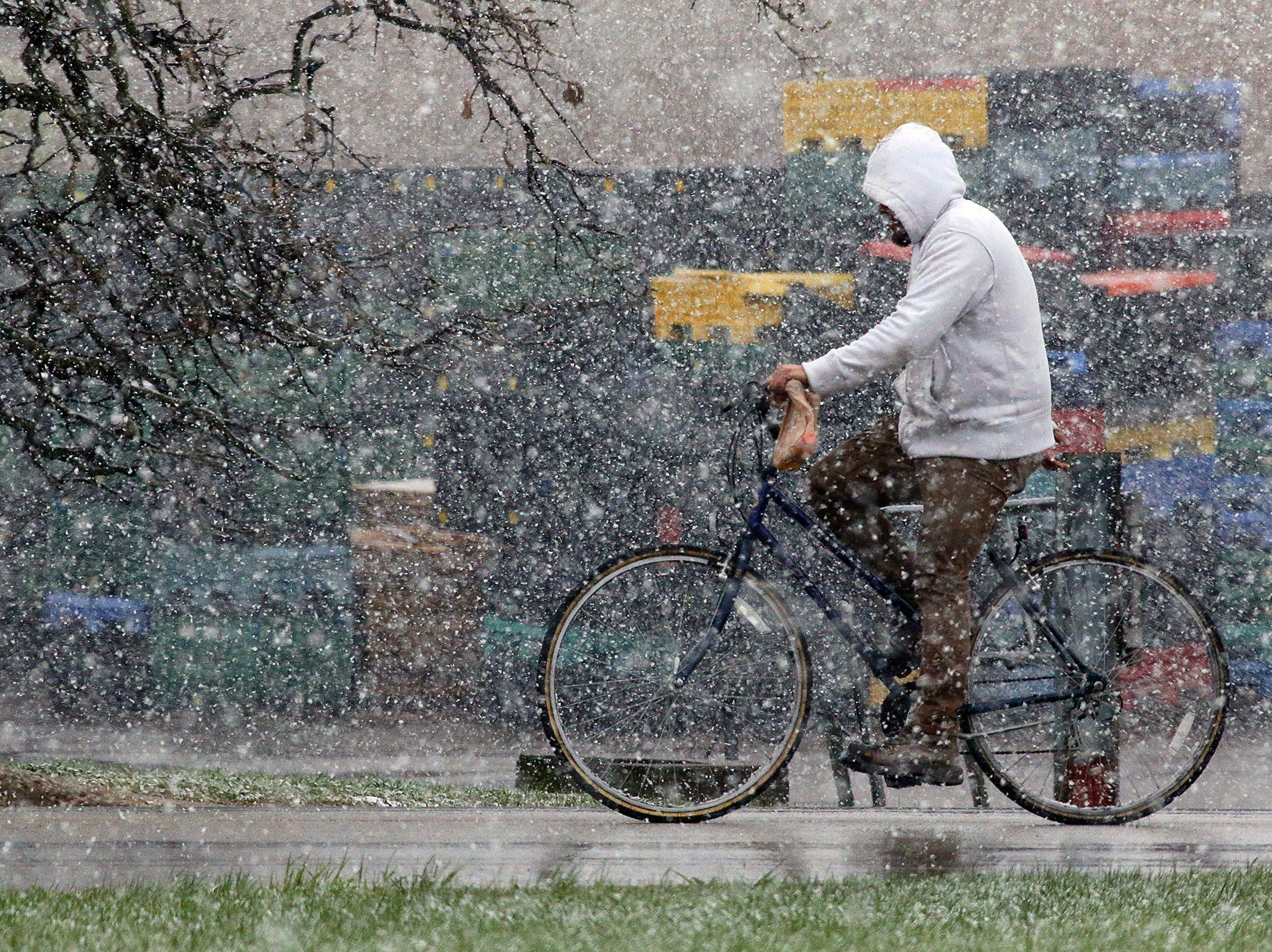 A man rides his bike through the snow along Allanson Road in Mundelein, Ill. Saturday morning, April 27, 2019.