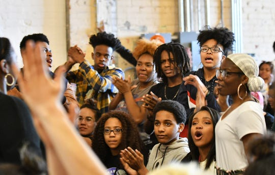 """Fellow poets and audience members applaud after the poem by Kennedy Byrd of the Detroit Youth Poetry Slam team at the """"Louder Than a Bomb"""" poetry festival at MOCAD."""