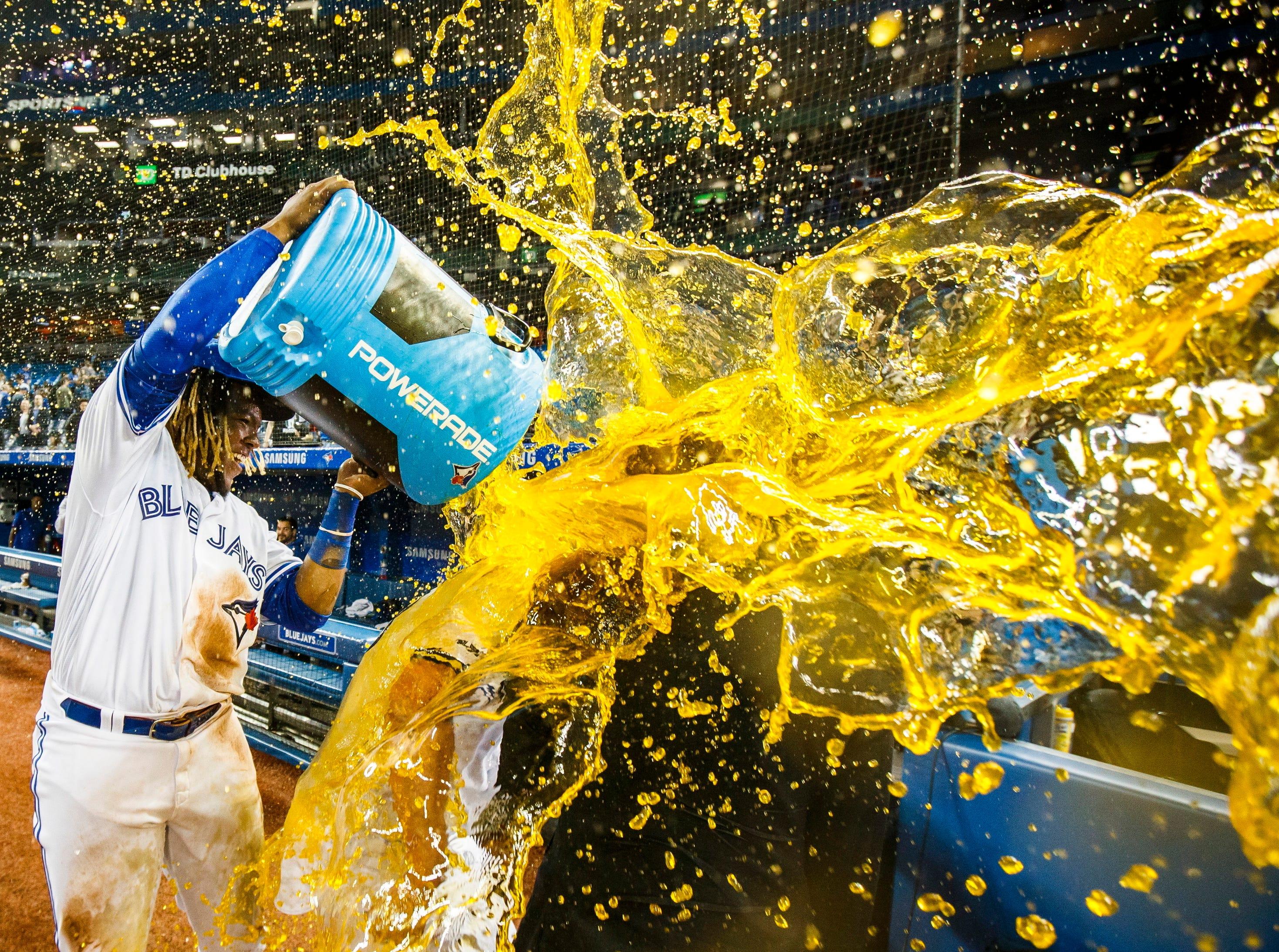 Toronto Blue Jays' Vladimir Guerrero Jr., left, douses teammate Brandon Drury after Drury's walkoff ninth-inning home run to defeat the Oakland Athletics in Toronto, Friday, April 26, 2019.