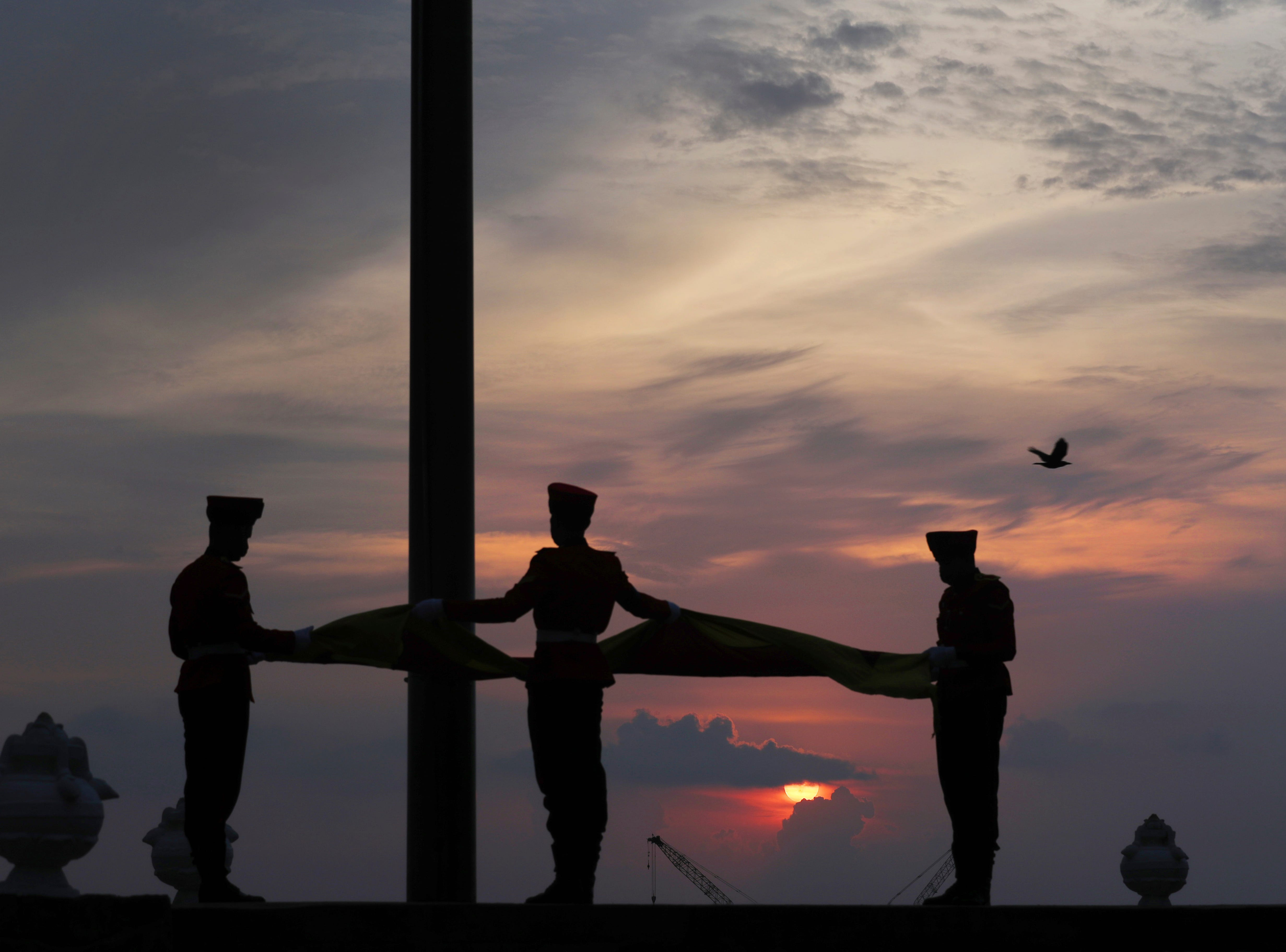 Soldiers lower the national flag as the sun sets on Sunday in Colombo, Sri Lanka, April 28, 2019. In a rare show of unity, Sri Lankan President Maithripala Sirisena, Prime Minister Ranil Wickremesinghe and opposition leader Mahinda Rajapaksa attended the Sunday Mass in person. Their political rivalry and government dysfunction are blamed for a failure to act upon near-specific information received from foreign intelligence agencies that preceded the bombings, which targeted three churches and three luxury hotels.