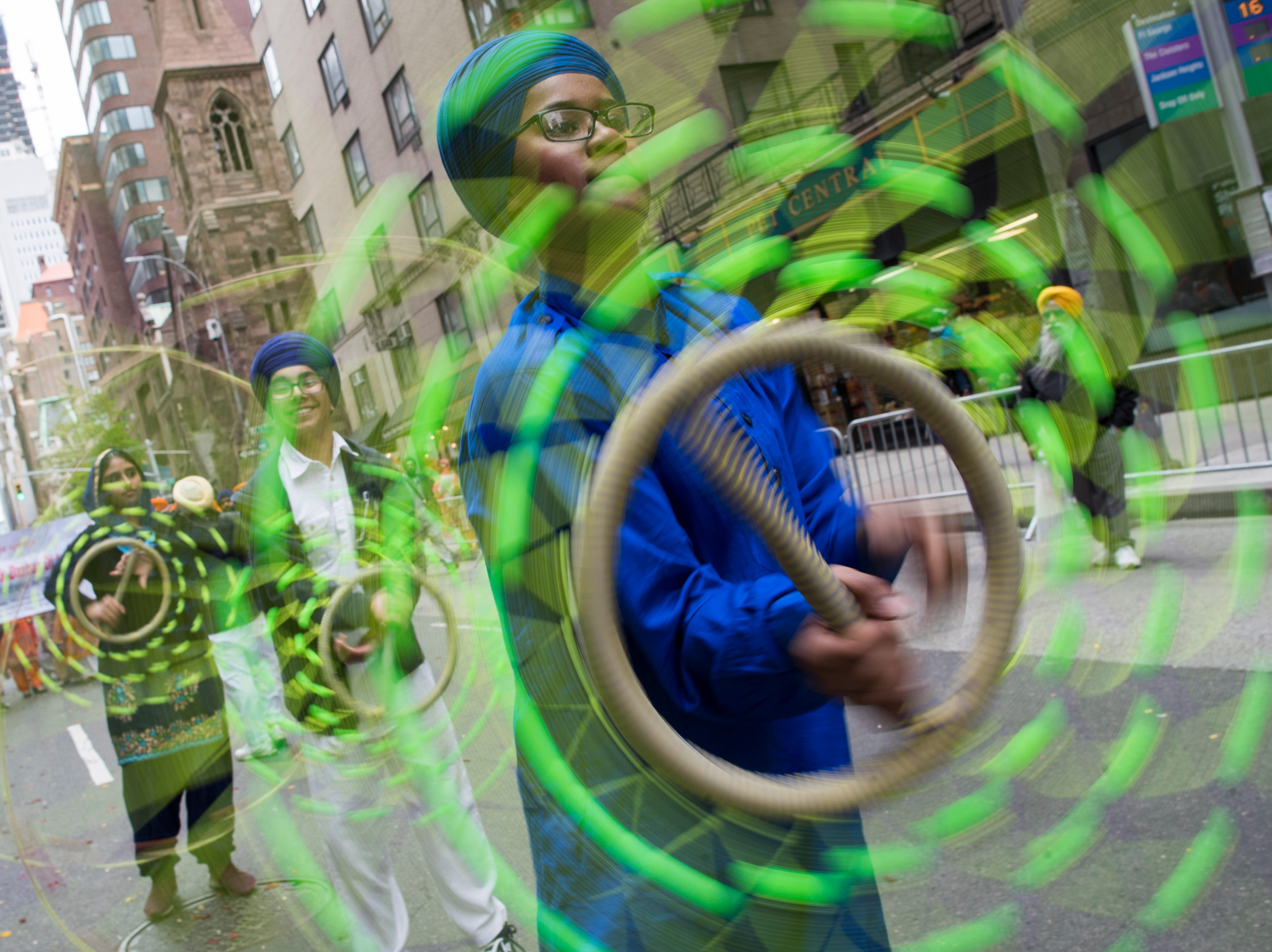 Participants twirl Shastars, a weapon used in the martial art Gatka, during the Sikh Day Parade, celebrating the Sikh holiday of Vaisakhi, Saturday, April 27, 2019, in New York.
