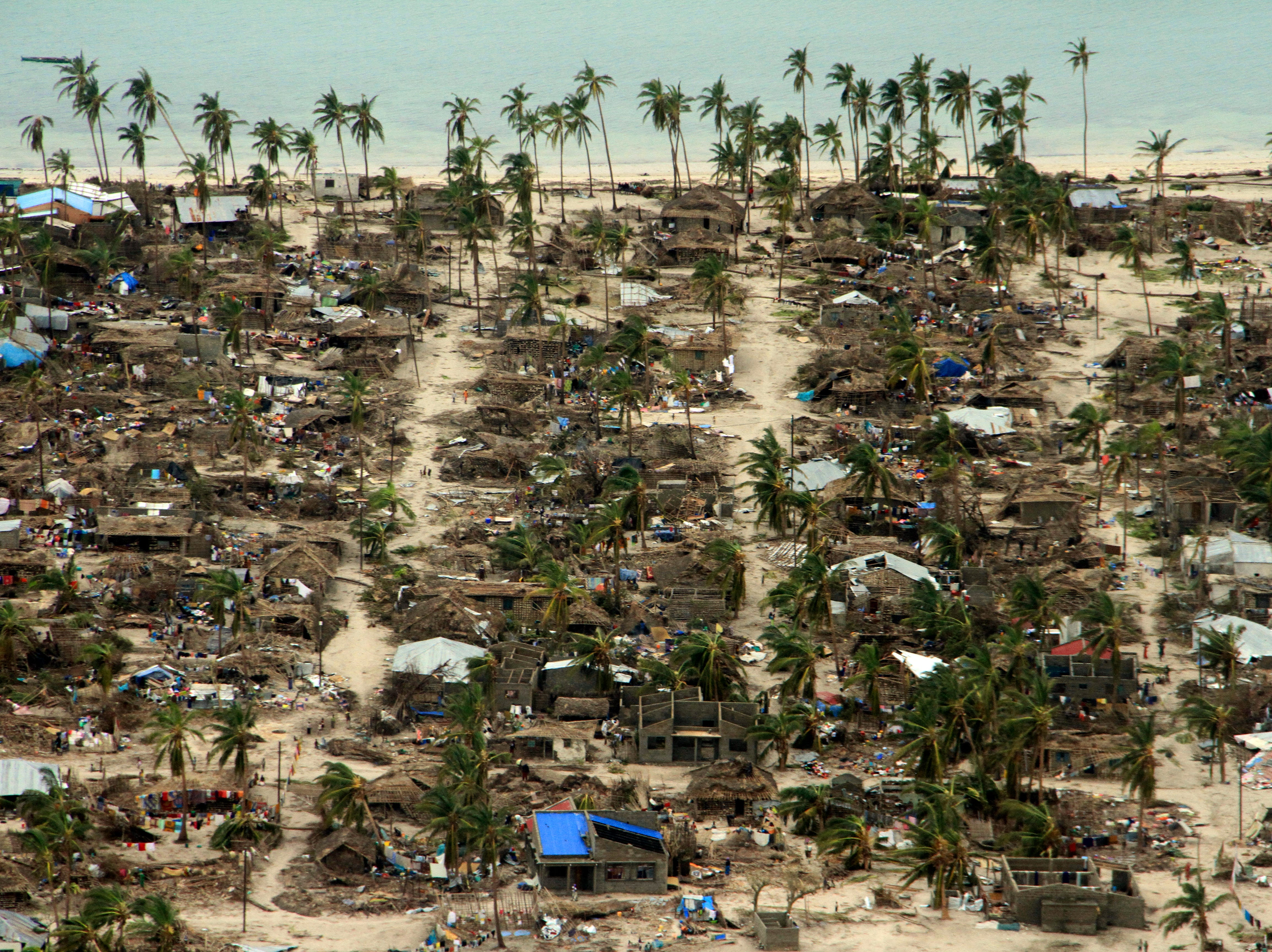 In this photo provided by the United Nations Office for the Coordination of Humanitarian Affairs (OCHA), badly damaged communities are seen from an aerial view, in Macomia district, Mozambique, on Saturday, April 27, 2019. Authorities have urged many residents to seek higher ground in the wake of Cyclone Kenneth as rain lashes the region.