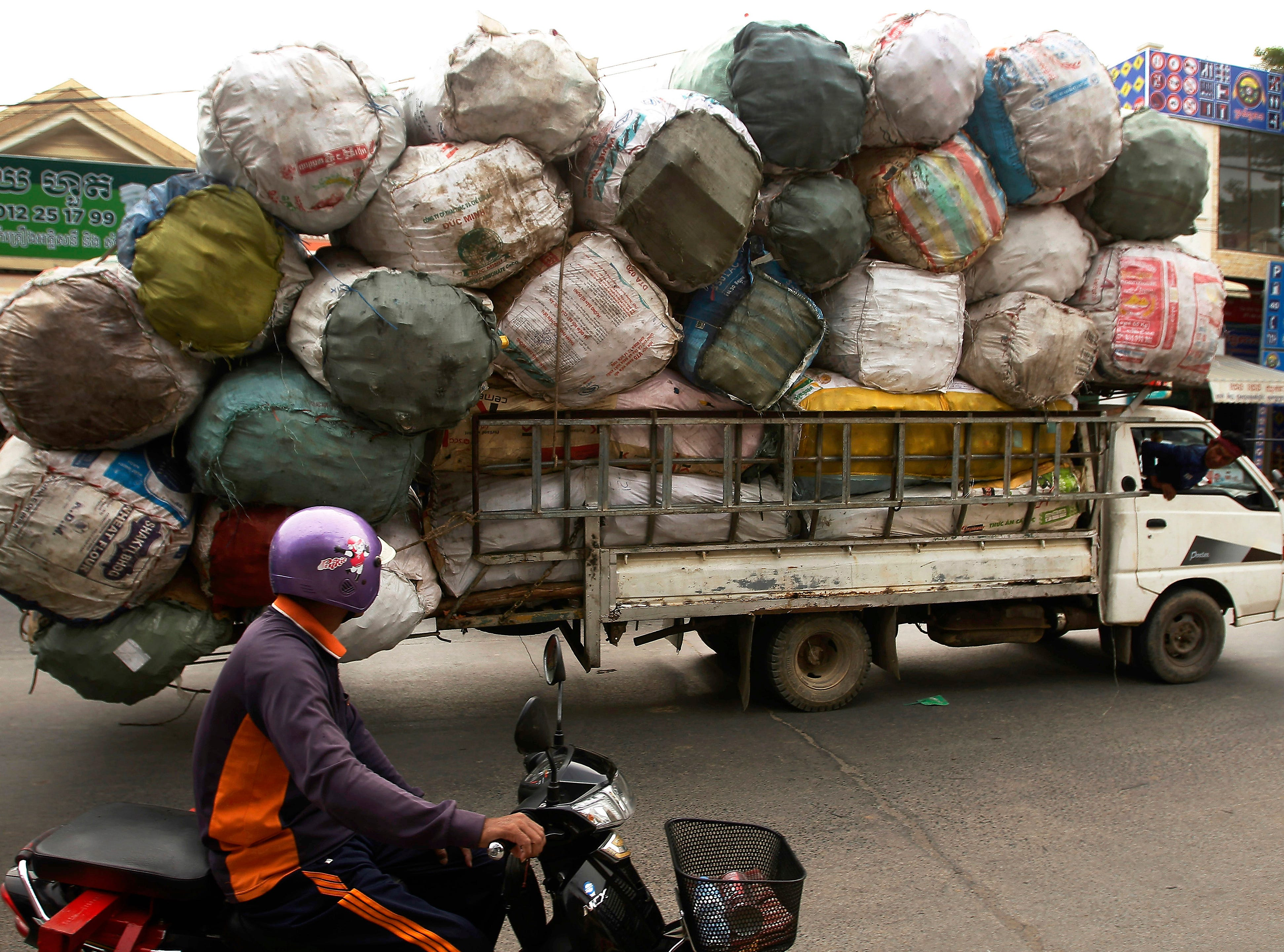 A truck overloaded with scrap materials passes by on a street in downtown Phnom Penh, Cambodia, Saturday, April 27, 2019.