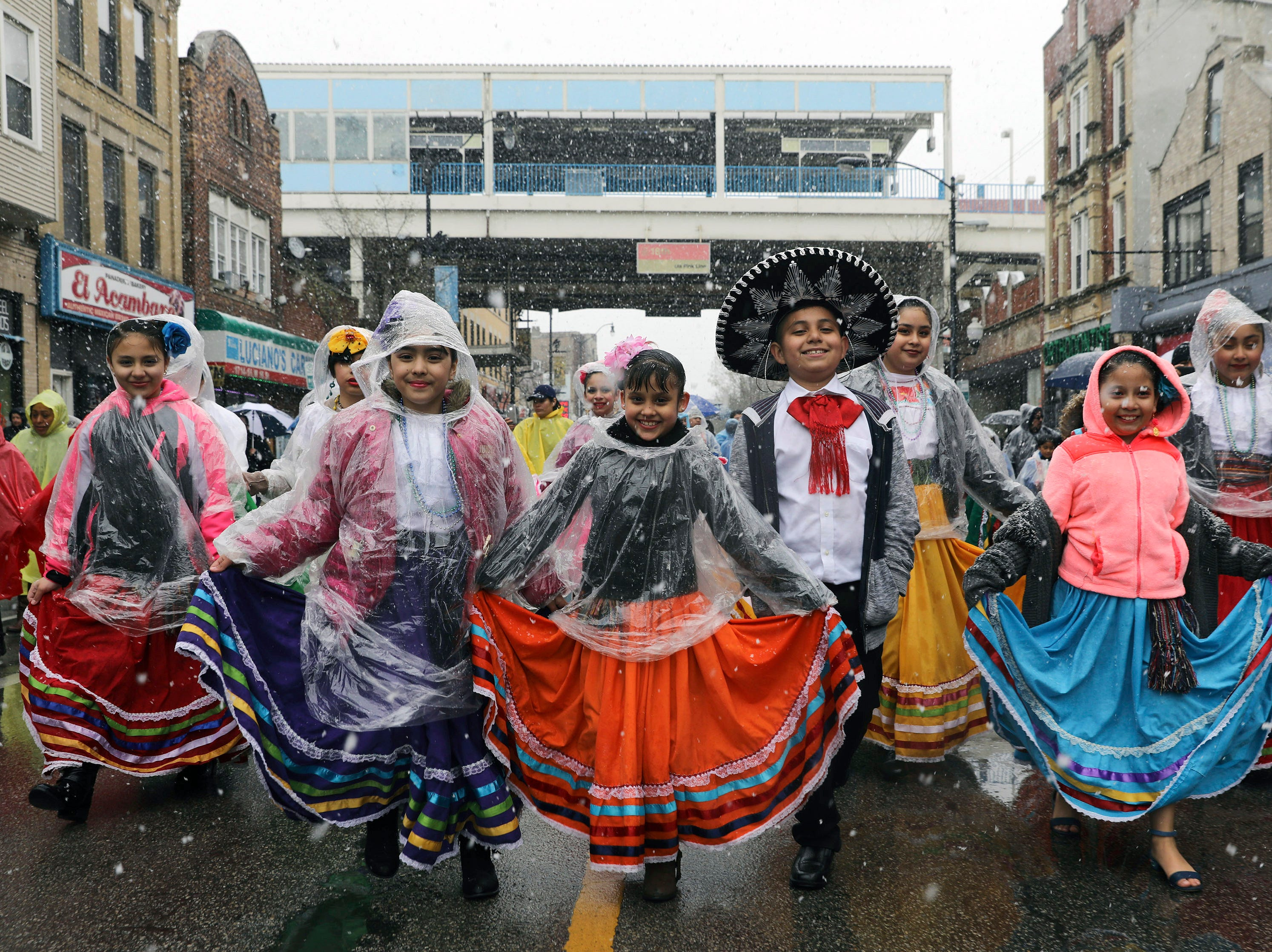 """Children in Mexican folklore outfits brave inclement weather to participate in """"El Dia del Nino,"""" Day of the Child parade, in Pilsen, Ill.,  Saturday, April 27, 2019."""