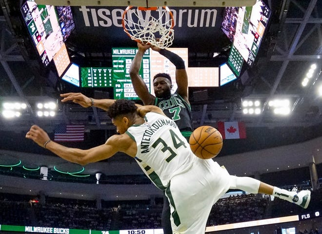 Boston's Jaylen Brown dunks over Milwaukee's Giannis Antetokounmpo during the second half of Game 1 on Sunday.