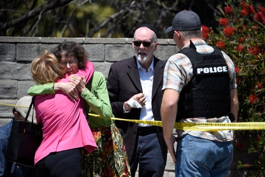 Two people hug as another talks to a San Diego County Sheriff's deputy outside of the Chabad of Poway synagogue, Saturday, April 27, 2019, in Poway, Calif.