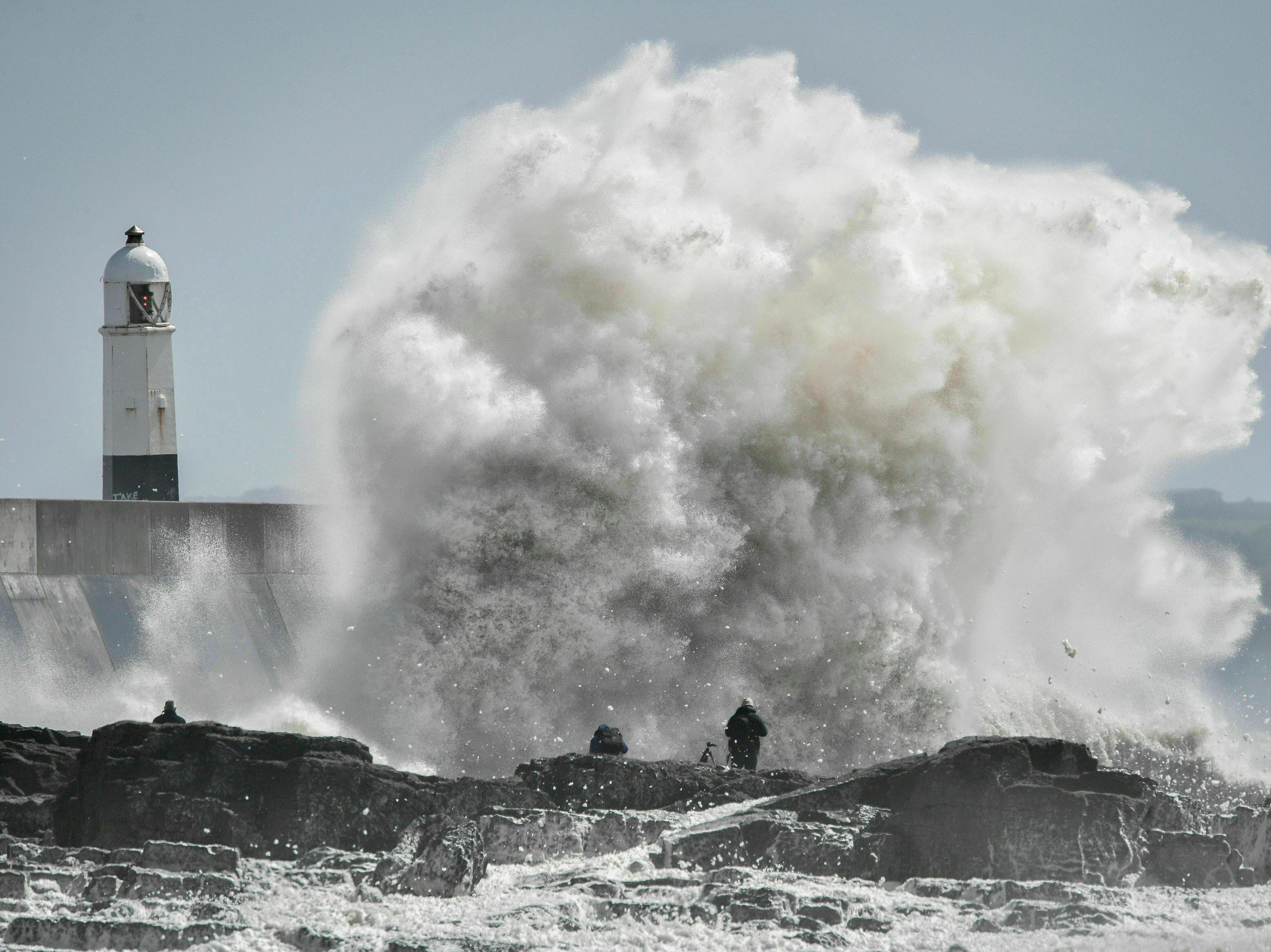 People watch huge waves crash against the shore at Porthcawl, Wales, where Storm Hannah is creating extremely strong gusts of wind, on Saturday, April 27, 2019.