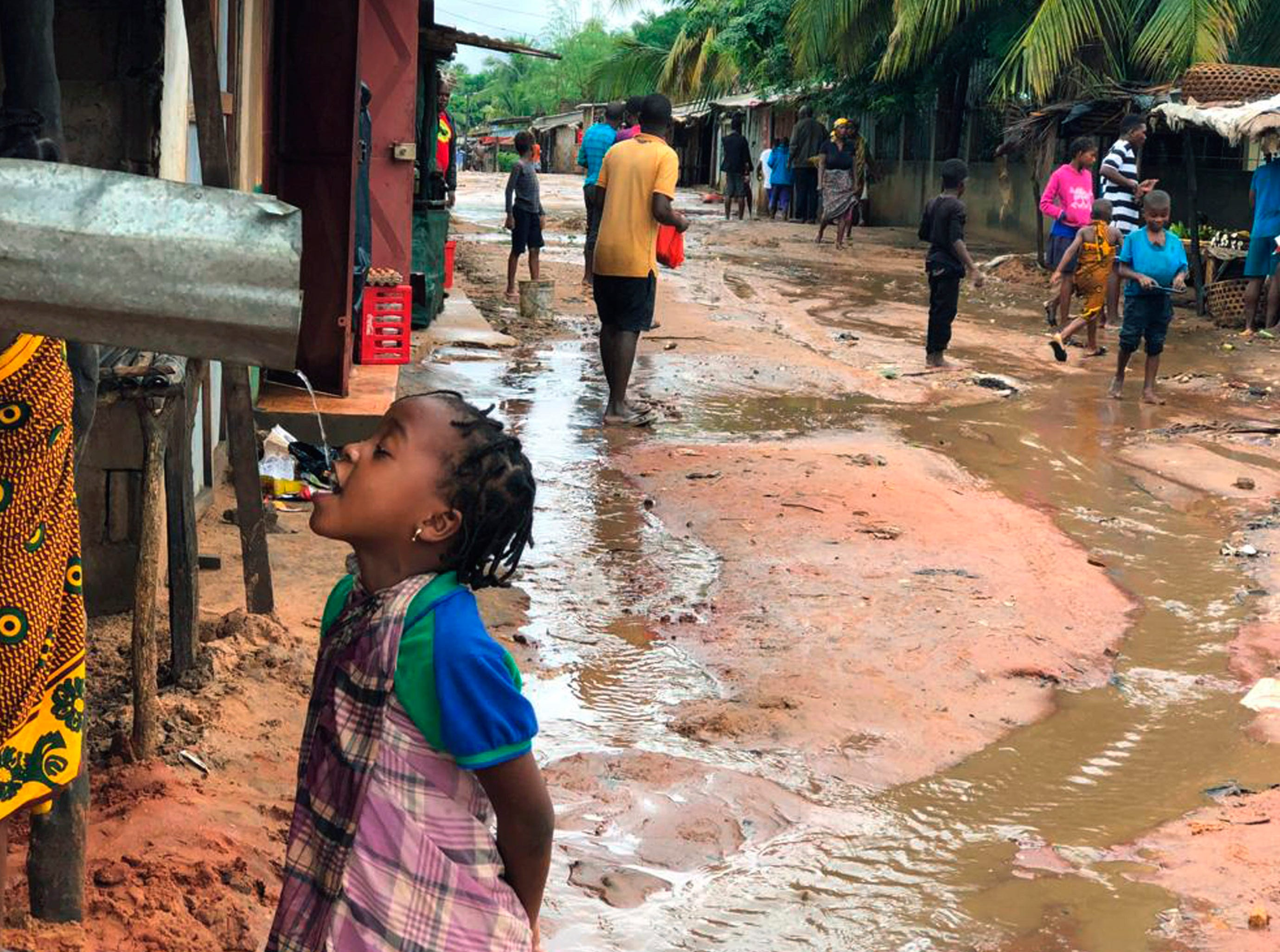 A child drinks from a gutter during floods from heavy rains in Pemba, Mozambique, Sunday, April 28, 2019. Serious flooding began on Sunday in parts of northern Mozambique that were hit by Cyclone Kenneth three days ago, with waters waist-high in areas, after the government urged many people to immediately seek higher ground. Hundreds of thousands of people were at risk.
