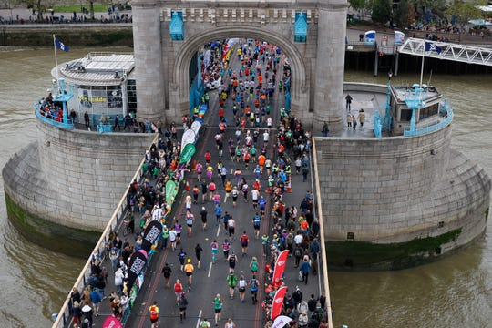 Competitors run across Tower Bridge as they compete in the 2019 London Marathon in central London on April 28, 2019.