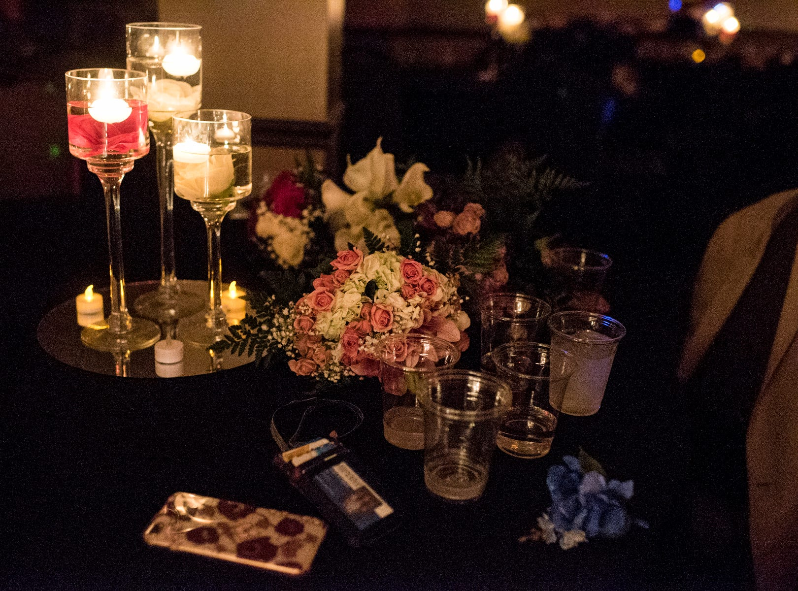 An assortment of water cups, cell phones, and flowers sit on a table as Evansville Day School students dance the night away during their prom held at the Hadi Shrine Banquet Hall in downtown Evansville, Ind., Saturday, April 27, 2019.