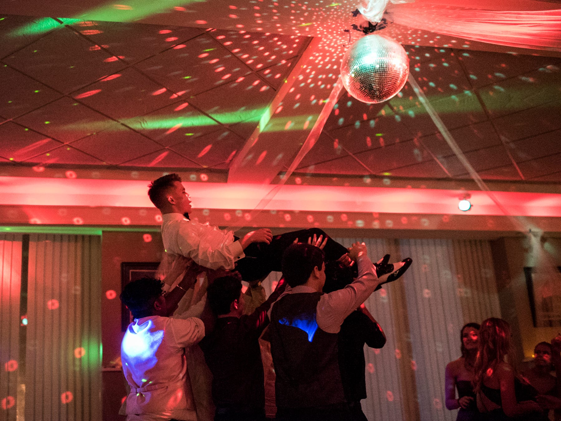Duke Moosbrugger steadies himself as a group of friends carry him across the dance floor during Evansville Day School's prom held at the Hadi Shrine Banquet Hall in downtown Evansville, Ind., Saturday, April 27, 2019.