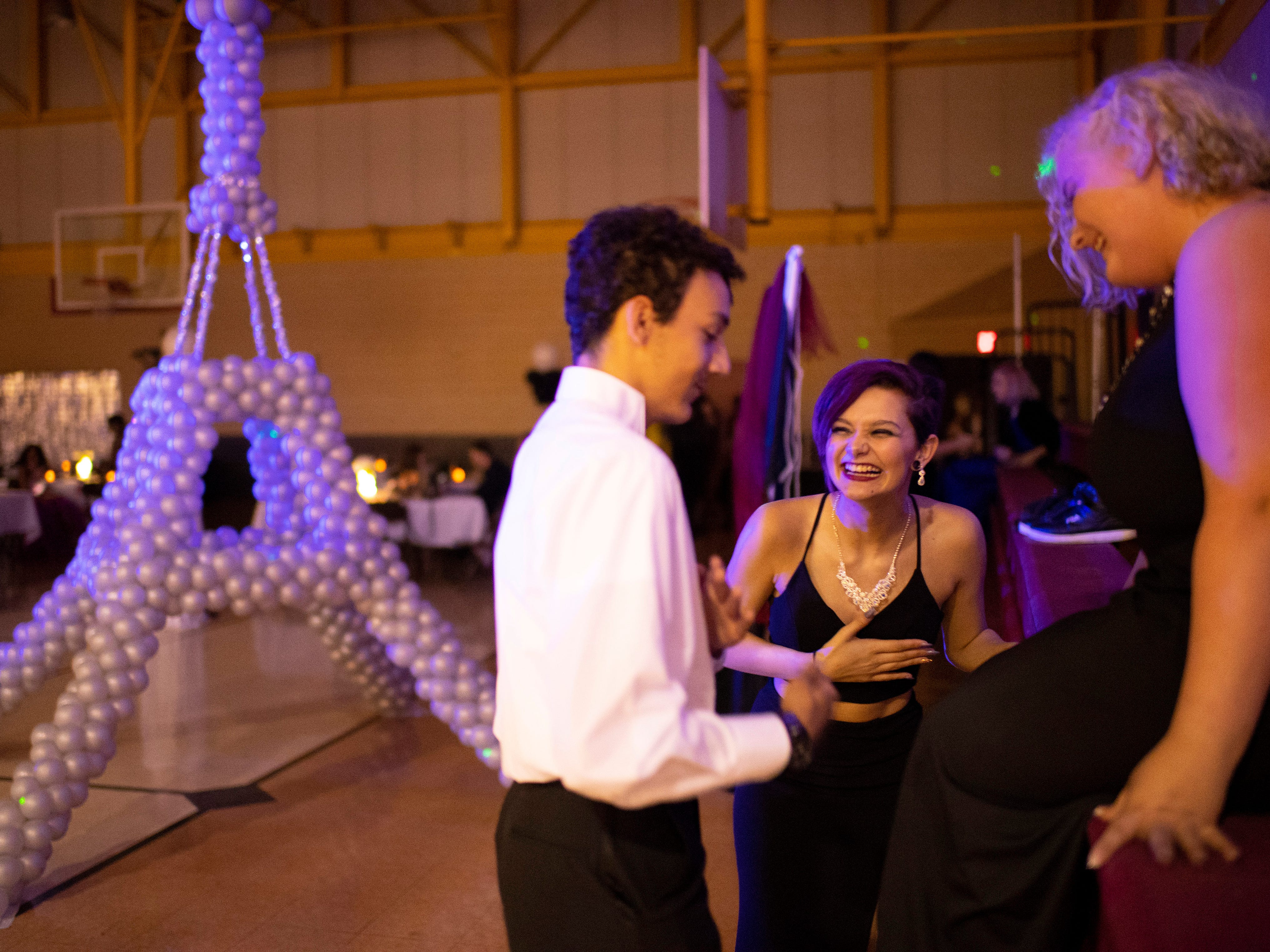 Students, from left, Hudson Kiesel, 17, Lillian Tirey, 17, and Megan Monroe, 17, dance near the bleachers during A Night in Paris at the Harwood Career Prep prom Saturday night.