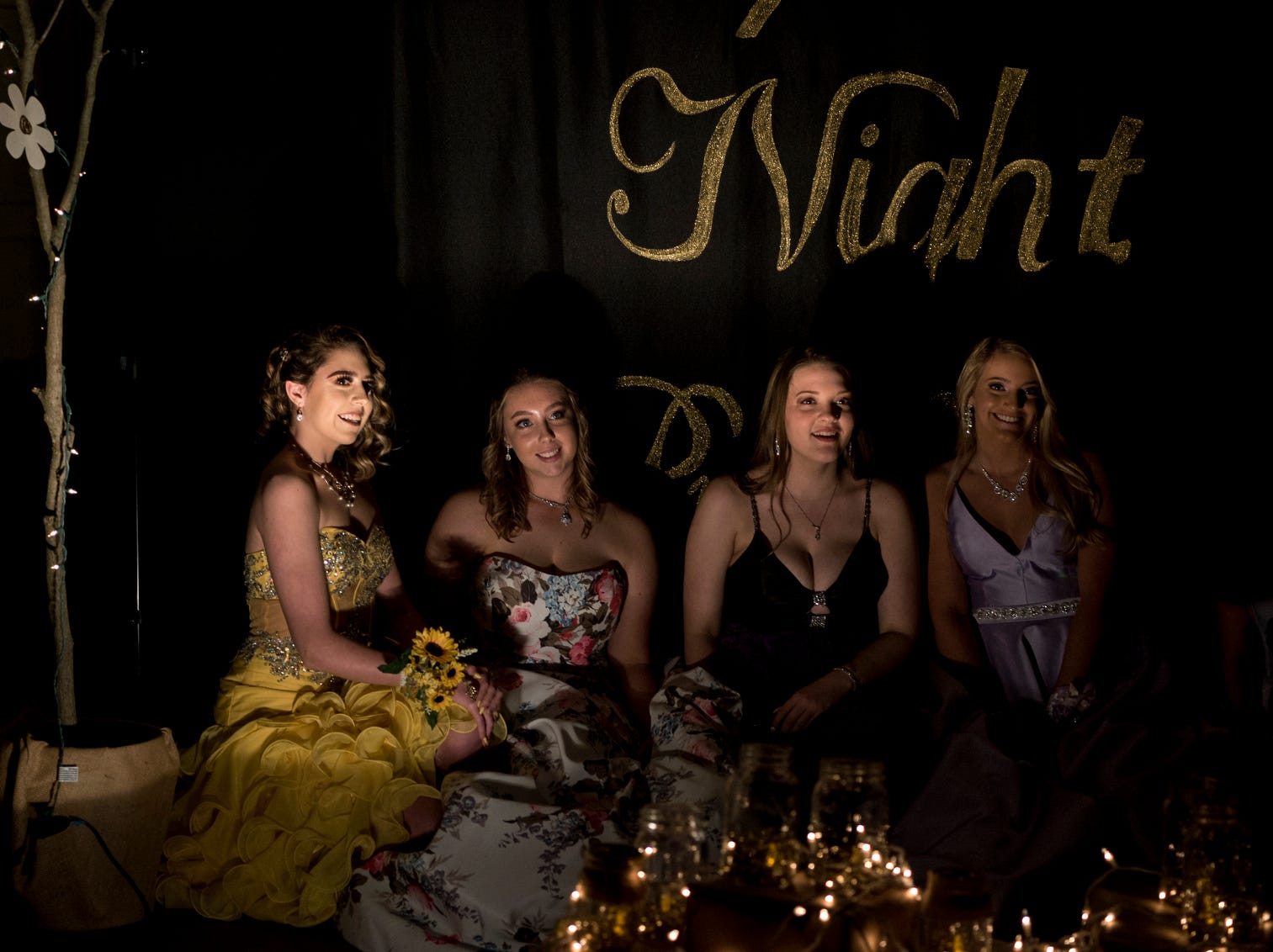 """Central High School students pose for a picture in front of a banner that reads """"Uptown Night Prom 2019"""" during the school's prom held at the Vanderburgh 4-H Center auditorium in Evansville, Ind., Saturday, April 27, 2019."""