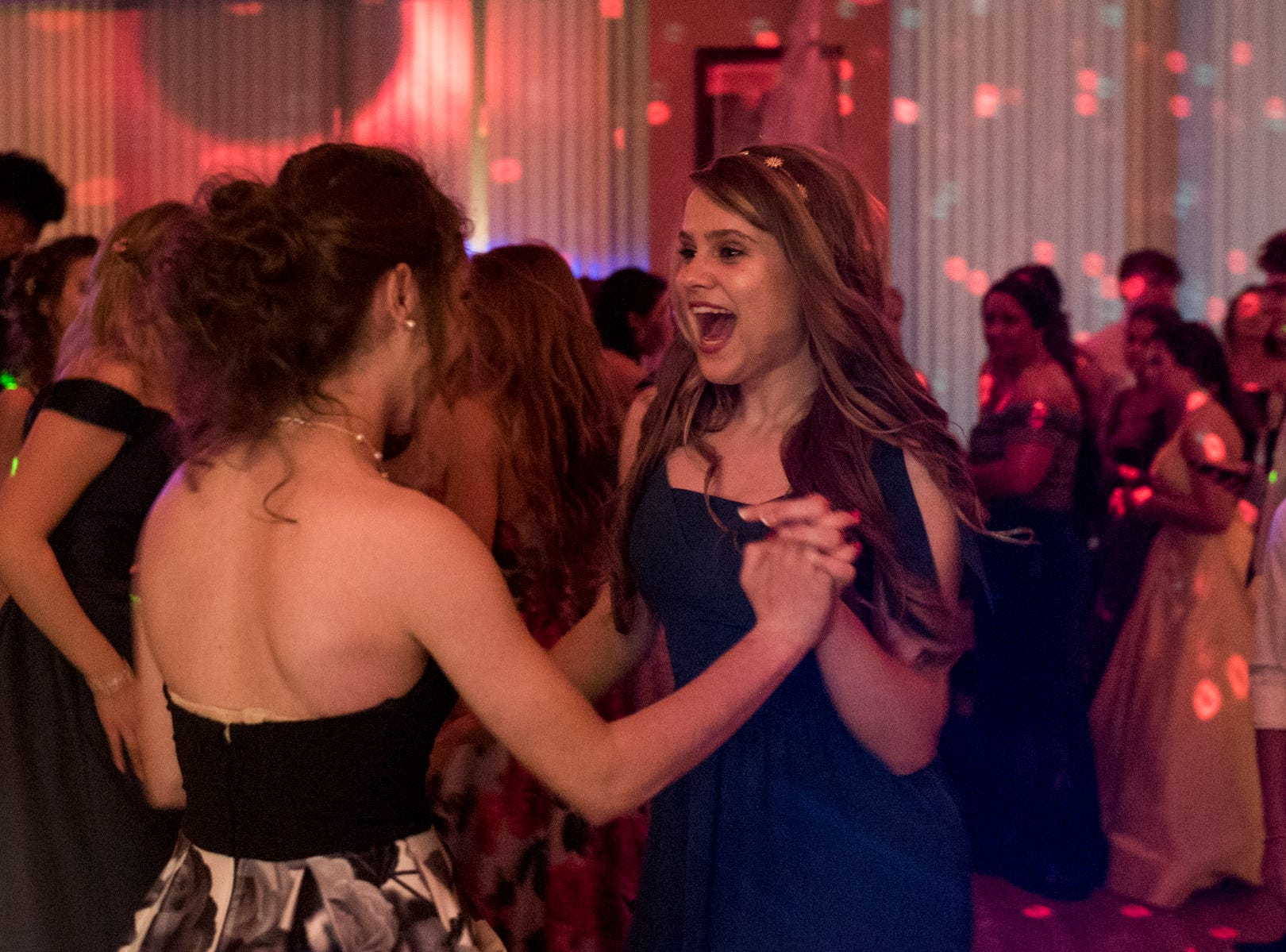 Lauren Goebel, left, and Adeleine Halsey, right, sing and dance together during Evansville Day School's prom held at the Hadi Shrine Banquet Hall in downtown Evansville, Ind., Saturday, April 27, 2019.