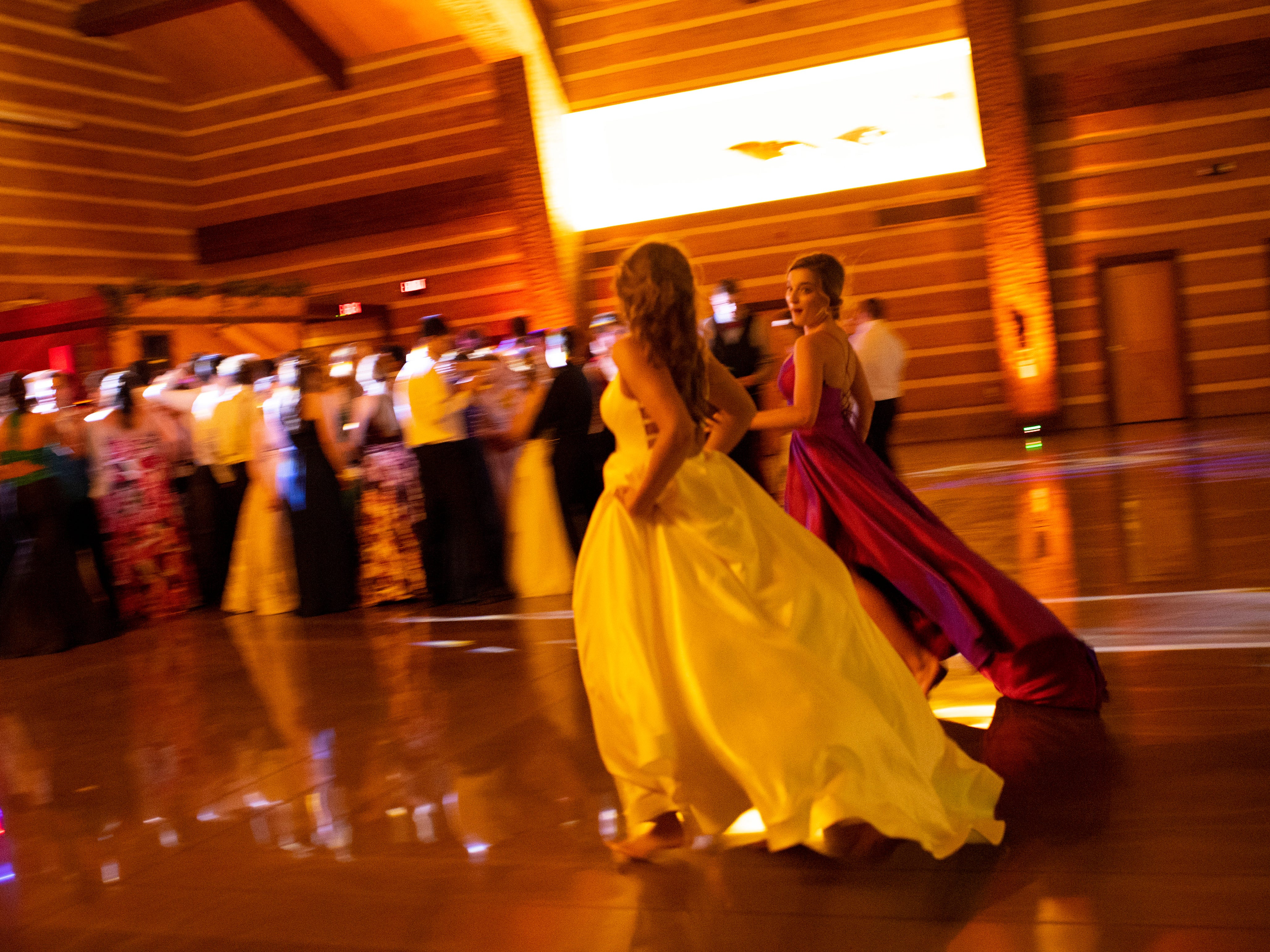 Attendees head to the stage area to dance at Mater Dei's prom at Burdette Park's Discovery Lodge Saturday night.