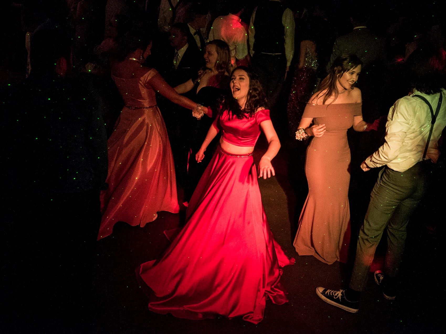 """Raya O'Brien, center, sings along to the song """"Bodak Yellow by Cardi B on the dance floor during Central High School's """"Uptown Night"""" themed prom held at the Vanderburgh 4-H Center auditorium in Evansville, Ind., Saturday, April 27, 2019."""