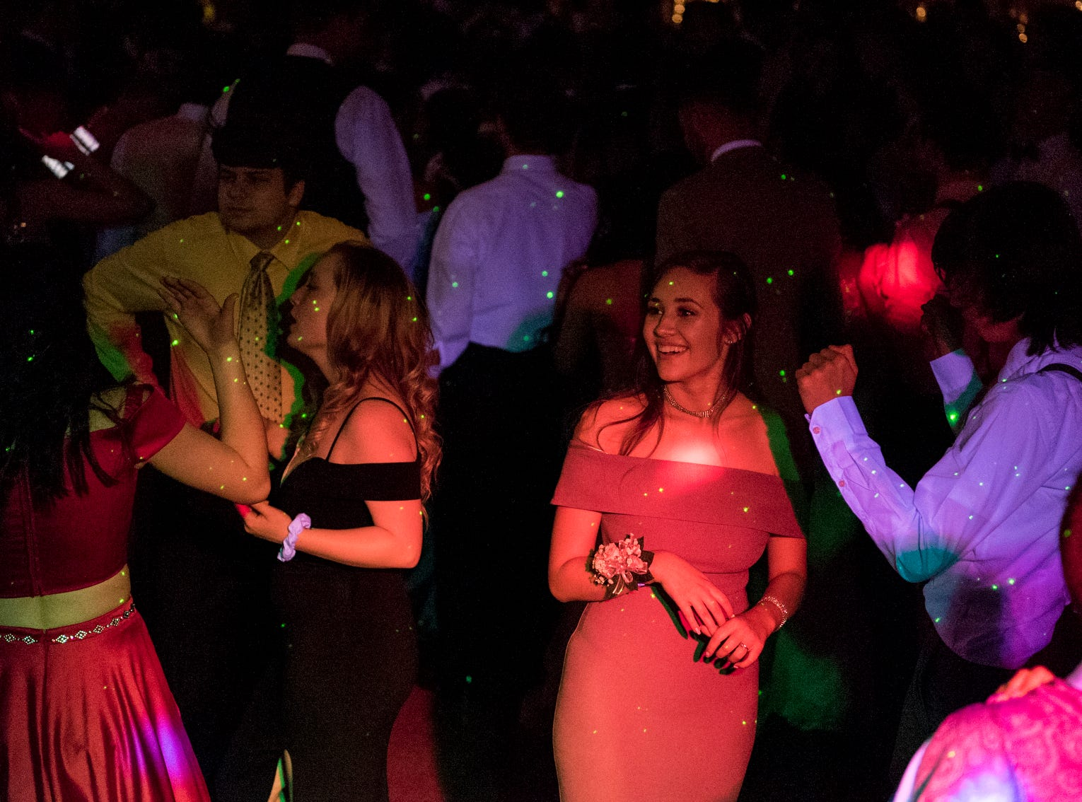 """Jasmine Richardson, center, smiles as she dances with her date Mason Bradley, right, and their friends during Central High School's """"Uptown Night"""" themed prom held at the Vanderburgh 4-H Center auditorium in Evansville, Ind., Saturday, April 27, 2019."""