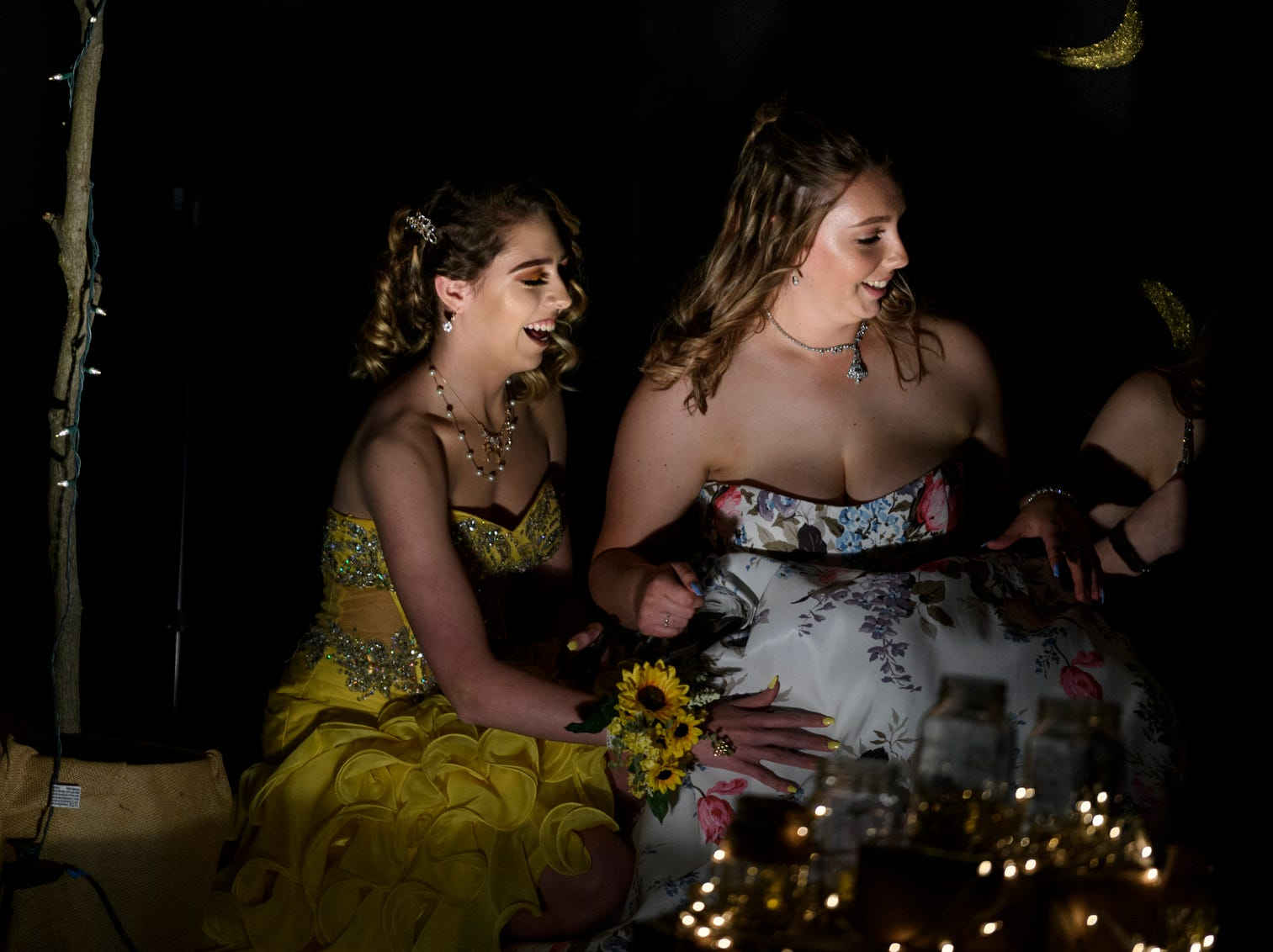 """Bailey Roby, left, and Olivia Gilham, right, laugh as they take a moment to situate themselves for a photo with friends in front of a banner during Central High School's """"Uptown Night"""" themed prom held at the Vanderburgh 4-H Center auditorium in Evansville, Ind., Saturday, April 27, 2019."""
