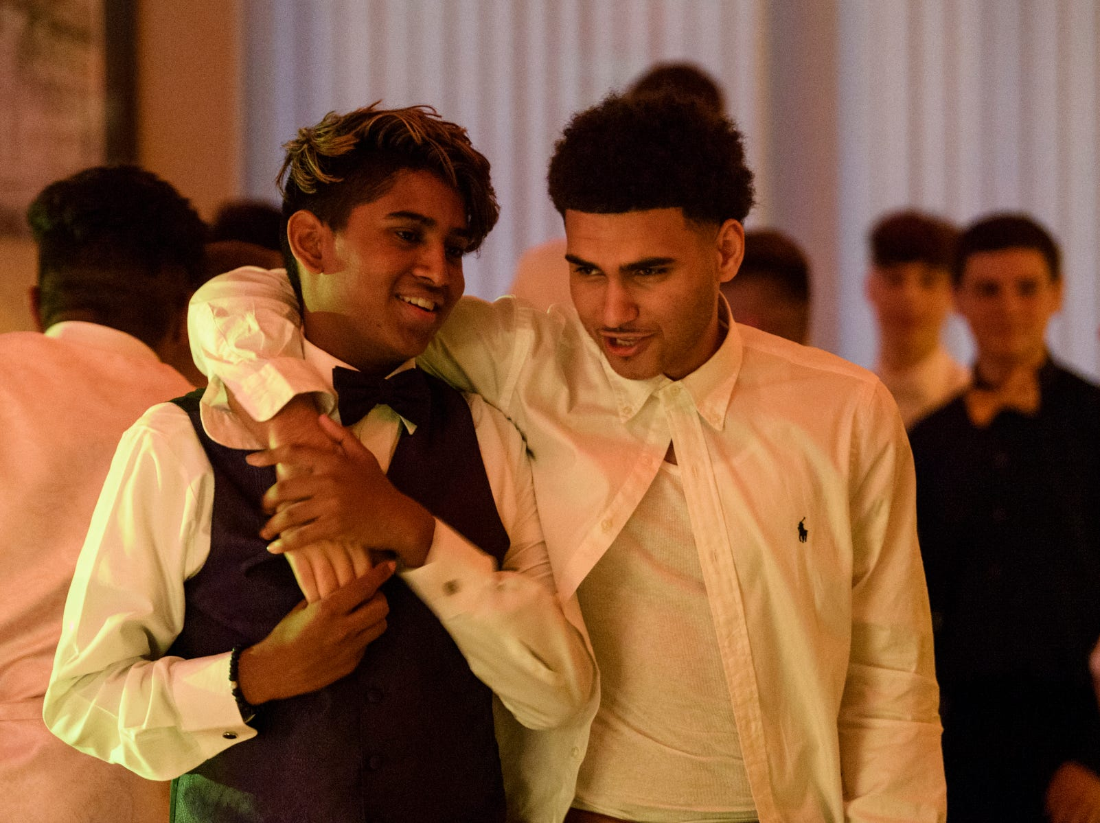 Dylan Kanetkar, left, and Cameron Monroe, right, chat as they walk off the dance floor during Evansville Day School's prom held at the Hadi Shrine Banquet Hall in downtown Evansville, Ind., Saturday, April 27, 2019.