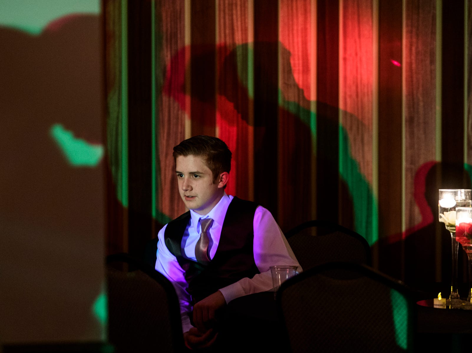 Colton Marvell takes a break to rest his feet as he watches other students dance during Evansville Day School's prom held at the Hadi Shrine Banquet Hall in downtown Evansville, Ind., Saturday, April 27, 2019.