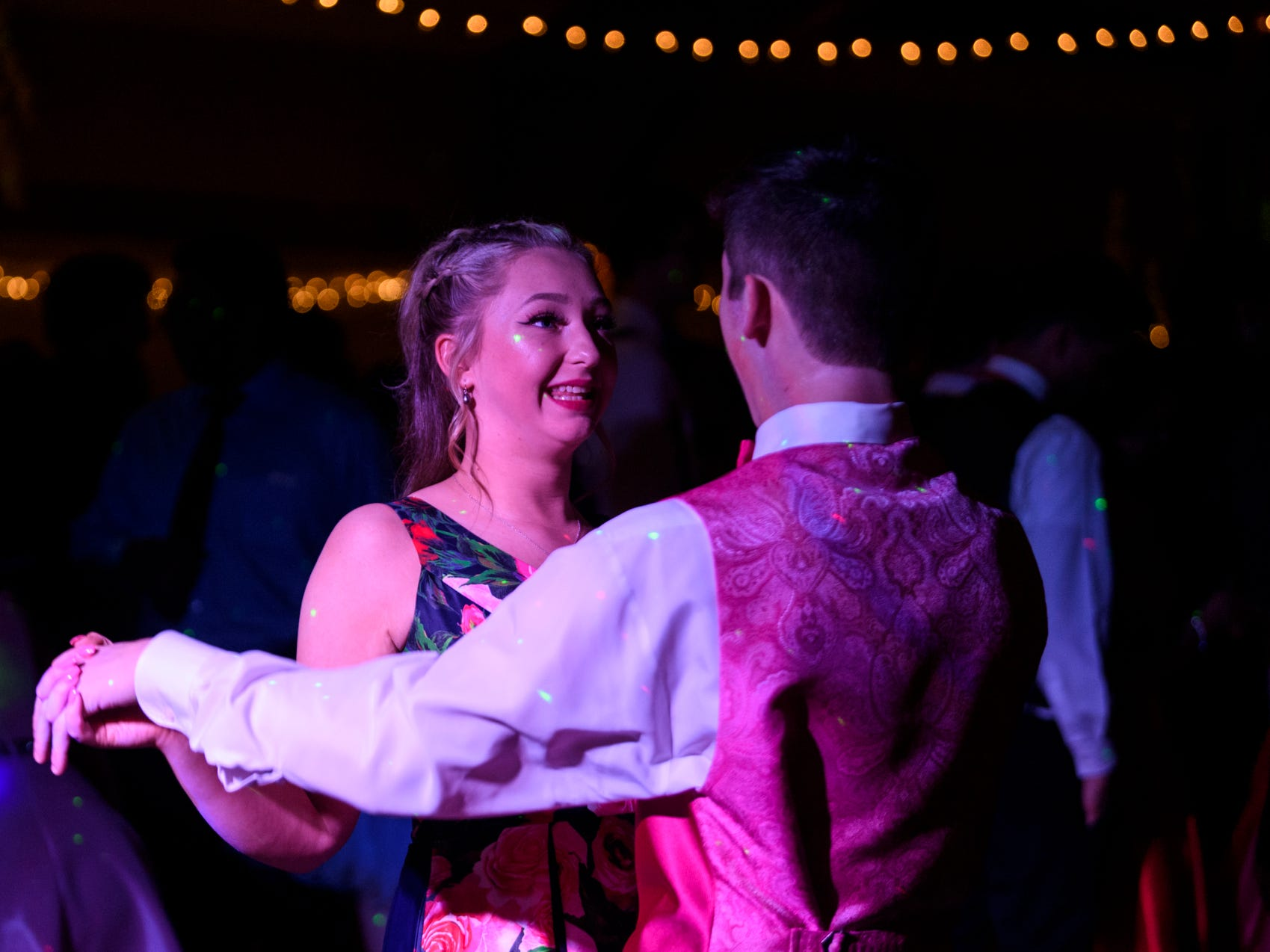 """Destiny Woods smiles as her date Jimmy Garris sings along to a song on the dance floor during Central High School's """"Uptown Night"""" themed prom held at the Vanderburgh 4-H Center auditorium in Evansville, Ind., Saturday, April 27, 2019."""