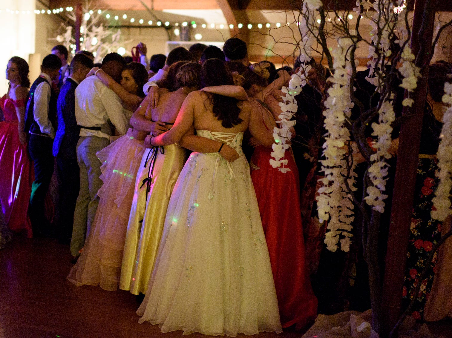 """Students huddle together and sway along to slow song on the dance floor during Central High School's """"Uptown Night"""" themed prom held at the Vanderburgh 4-H Center auditorium in Evansville, Ind., Saturday, April 27, 2019."""