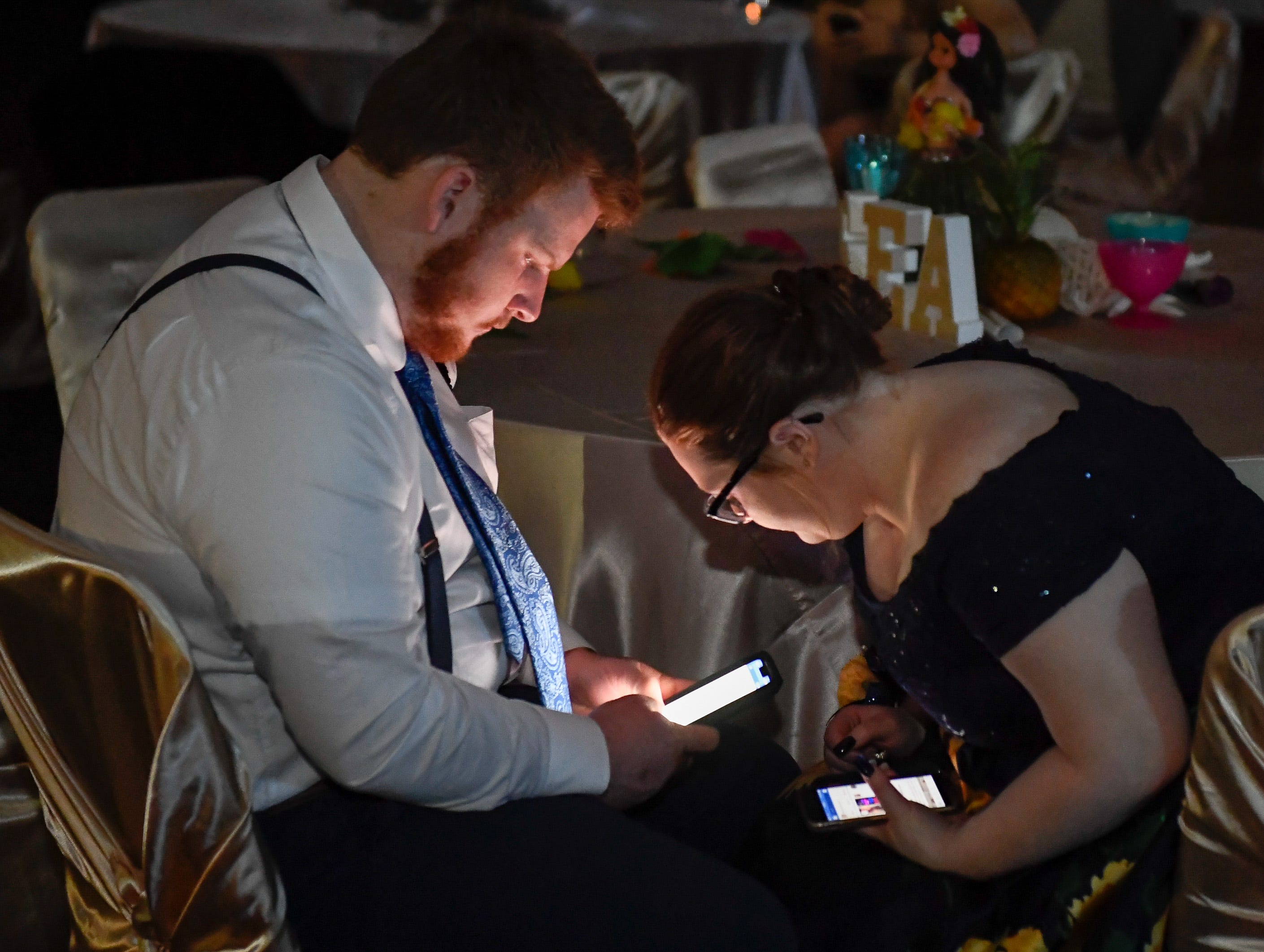 Michael Duncan and Kelsey Whitaker check their phones at the Castle High School prom, held at the Old National Events Center Plaza Saturday, April 27, 2019.