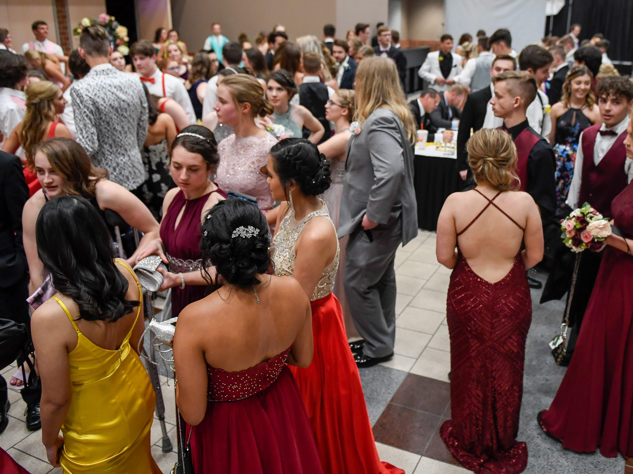 Couples gather in the lobby as they check into the Castle High School prom, held at the Old National Events Center Plaza Saturday, April 27, 2019.