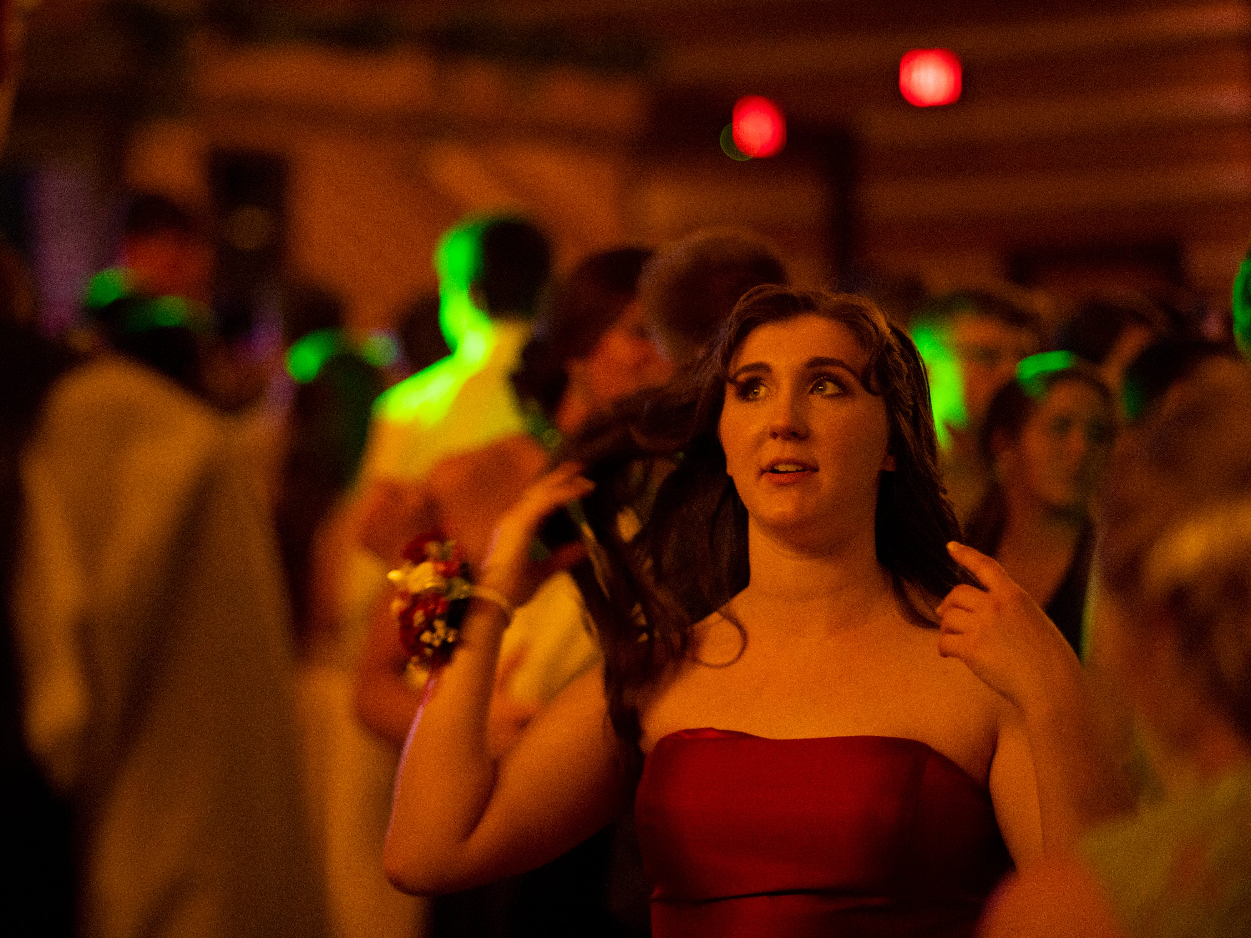 """Lydia Johnston, 17, dances to Ariana Grande's """"7 Rings"""" at Mater Dei's prom at Burdette Park's Discovery Lodge Saturday night."""