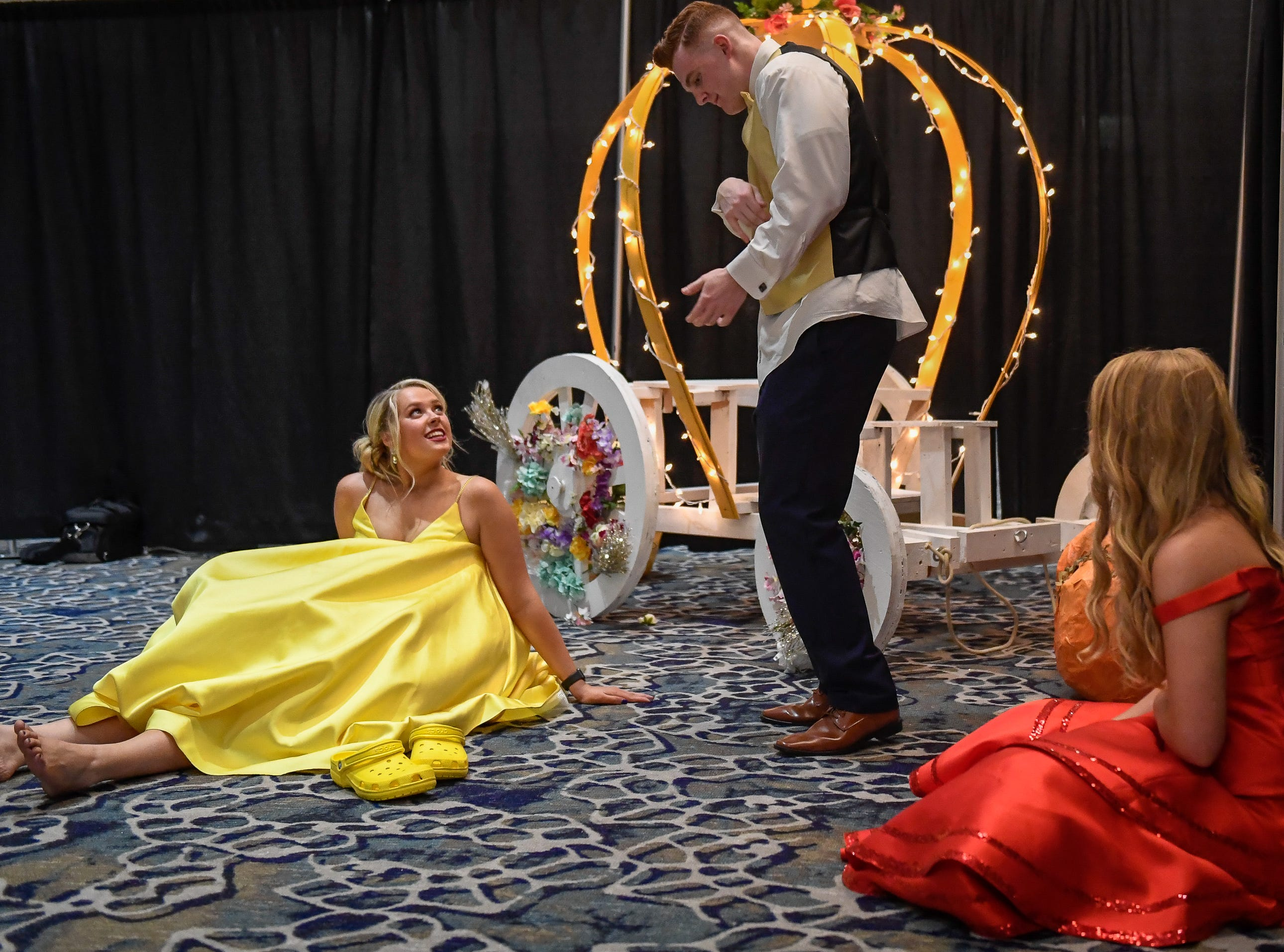 Max Green keeps the dancing going while Katelynn Davis, left, and Savannah Sullivan cool their heels at the Memorial High School prom, held at the Old National Events Center Plaza Saturday, April 27, 2019.