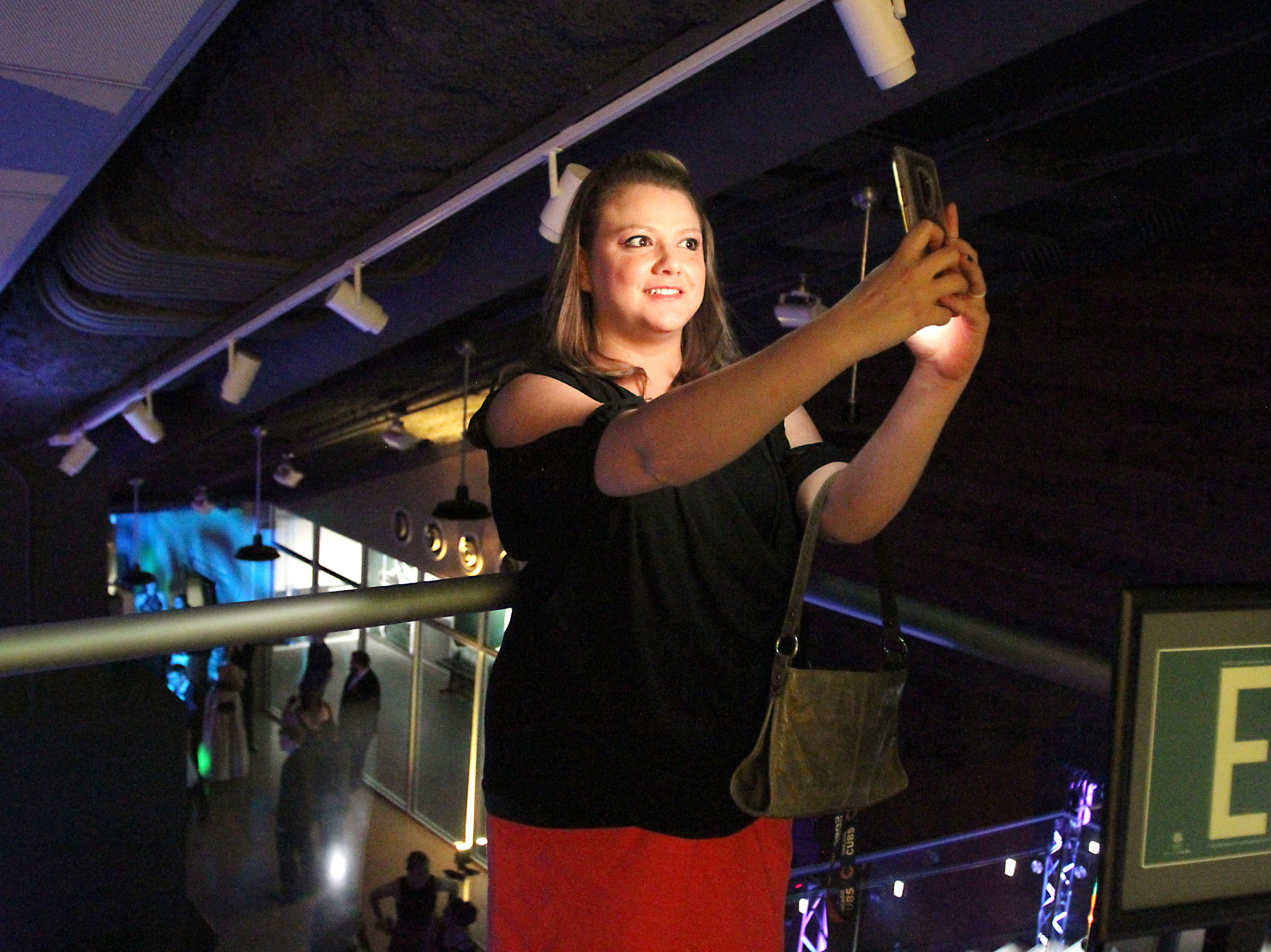 Joel Blocker / For the Coloradoan Liz Rodarte, who works in integrated services at Fort Collins, takes a moment to capture a selfie while chaperoning the LambkinsÕ prom held at Canvas stadium Saturday night.