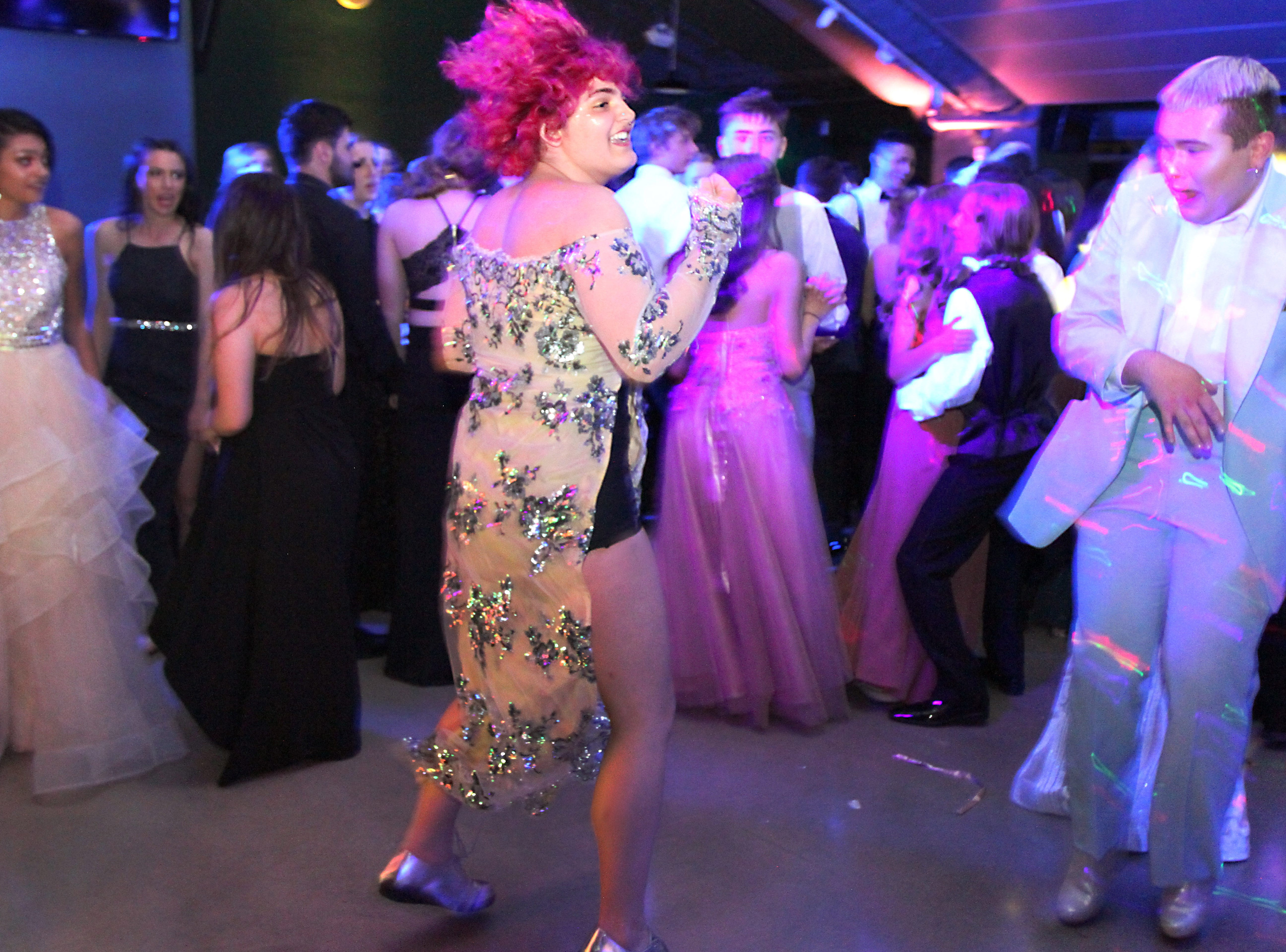 Joel Blocker / For the Coloradoan Gabrielle Herzman, middle, gets her groove on, while Zach Leerssen, right, looks on during the Fort Collins High School prom held at Canvas stadium Saturday night.