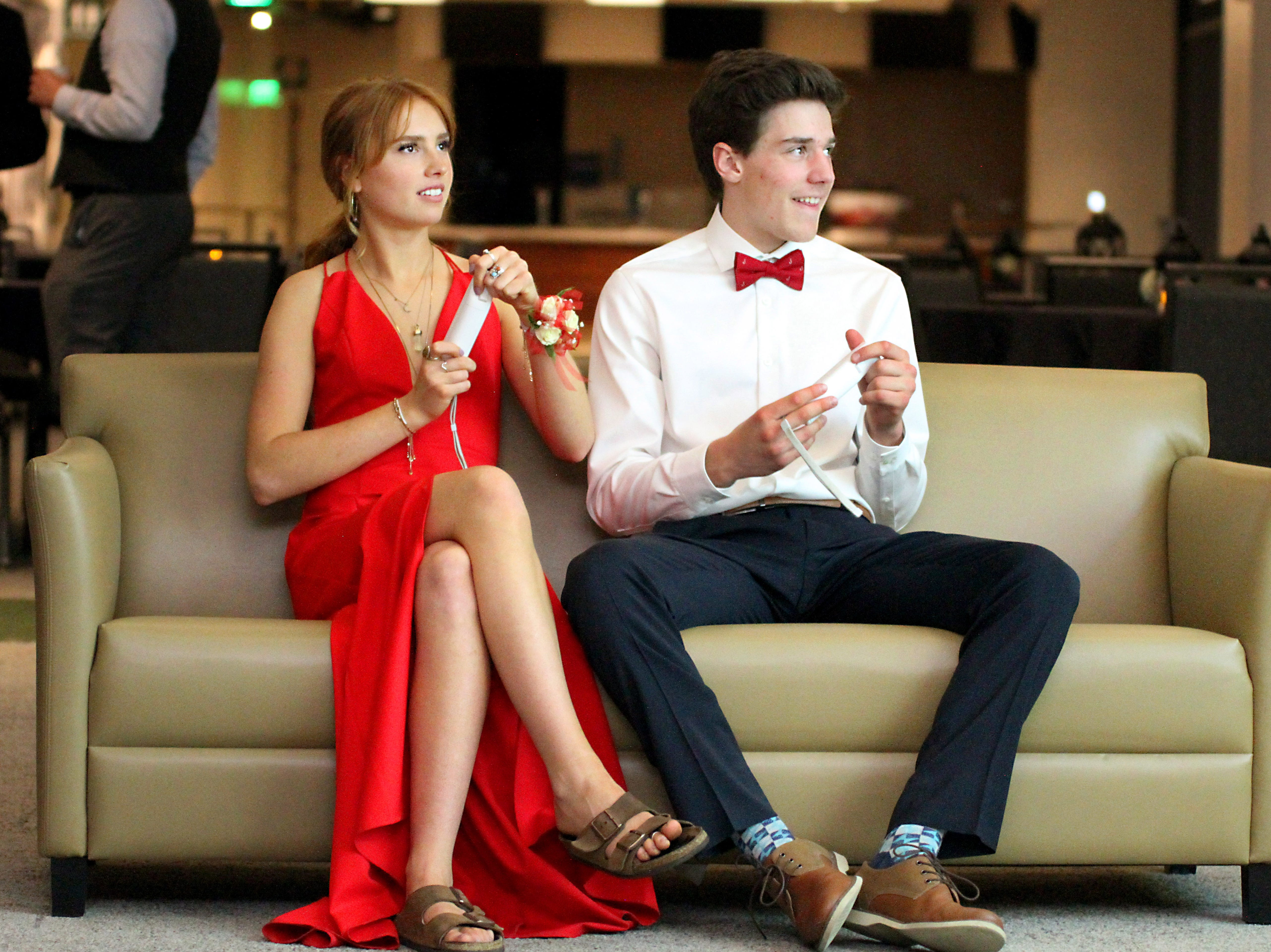 Joel Blocker / For the ColoradoanFort Collins High School seniors, Savannah Sanford and Will Lamperes, take a break from dancing to play video games during the Fort Collins High School prom held at Canvas stadium Saturday night.