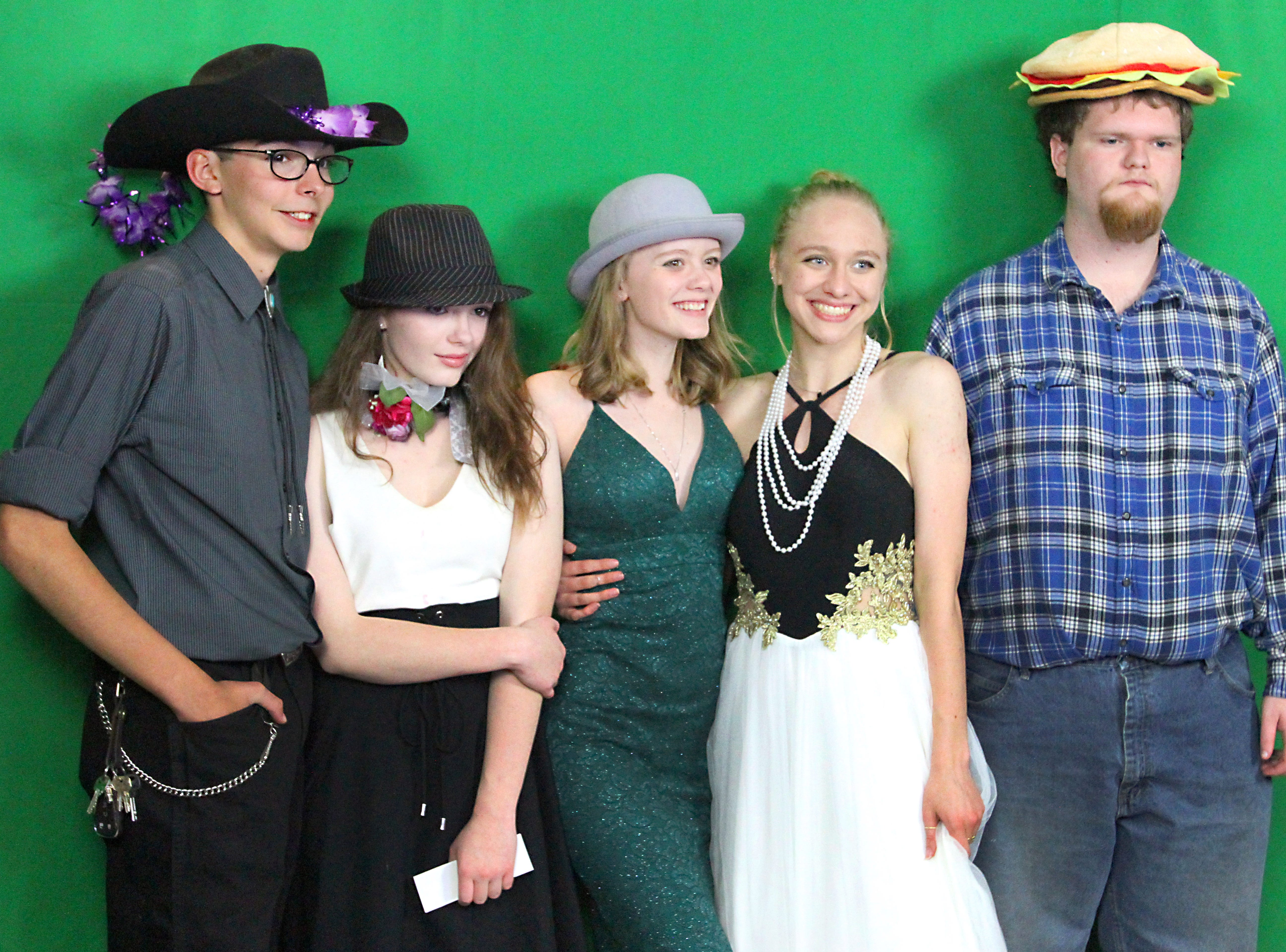 Joel Blocker / For the ColoradoanFort Collins high School students, from left, Joseph Schippers, Kelly Warden, Samantha Magill, Jennica Travis and Dalton Sandmann  pose in a front of a green screen while getting their pictures taken from a photo booth during the Fort Collins High School prom held at Canvas stadium Saturday night.