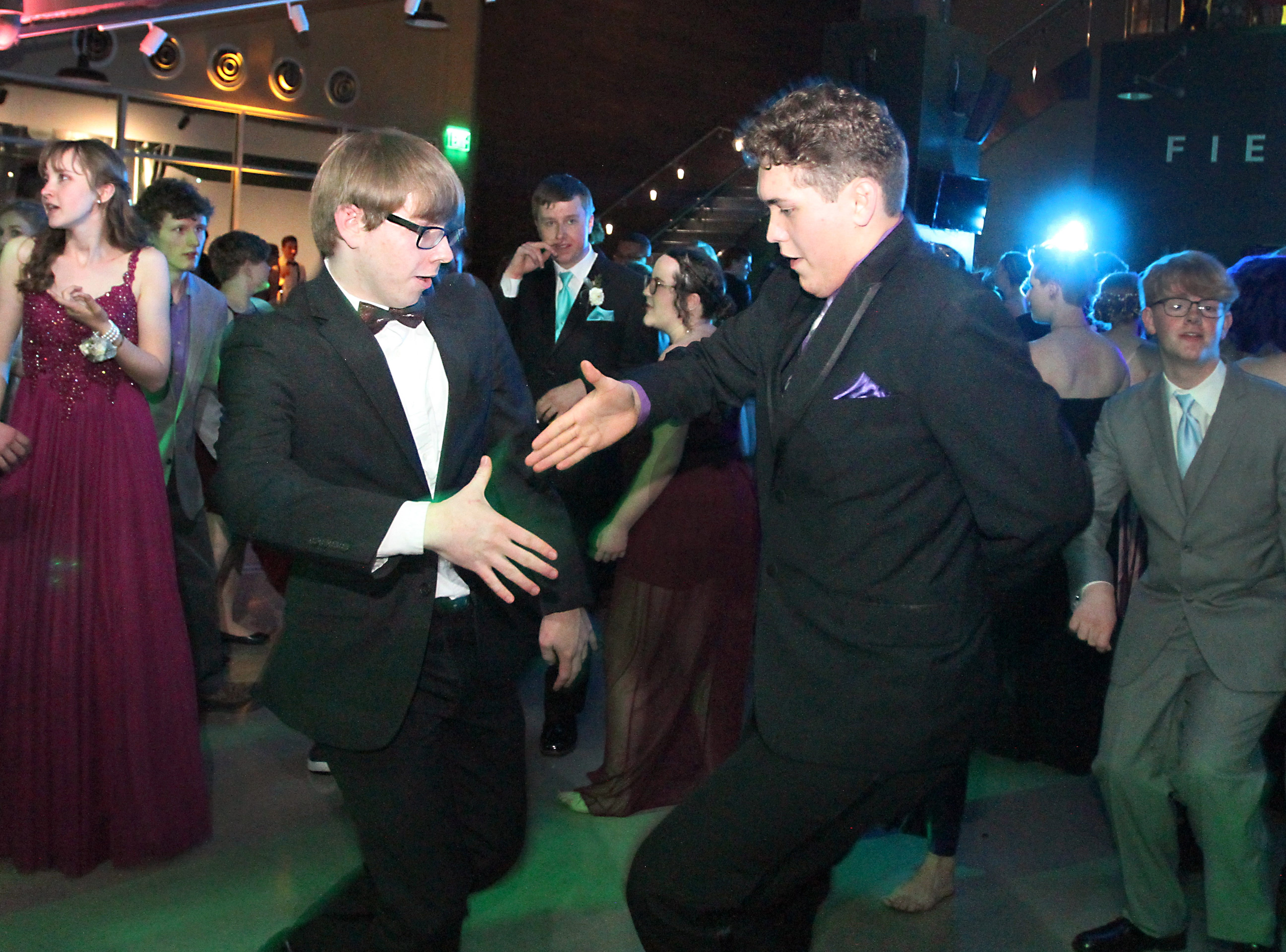 Fort Collins high School seniors, from left, Ian Wagers and Cameron Velez, go in for a high-five while grooving to the music during the Fort Collins High School prom held at Canvas stadium Saturday night.