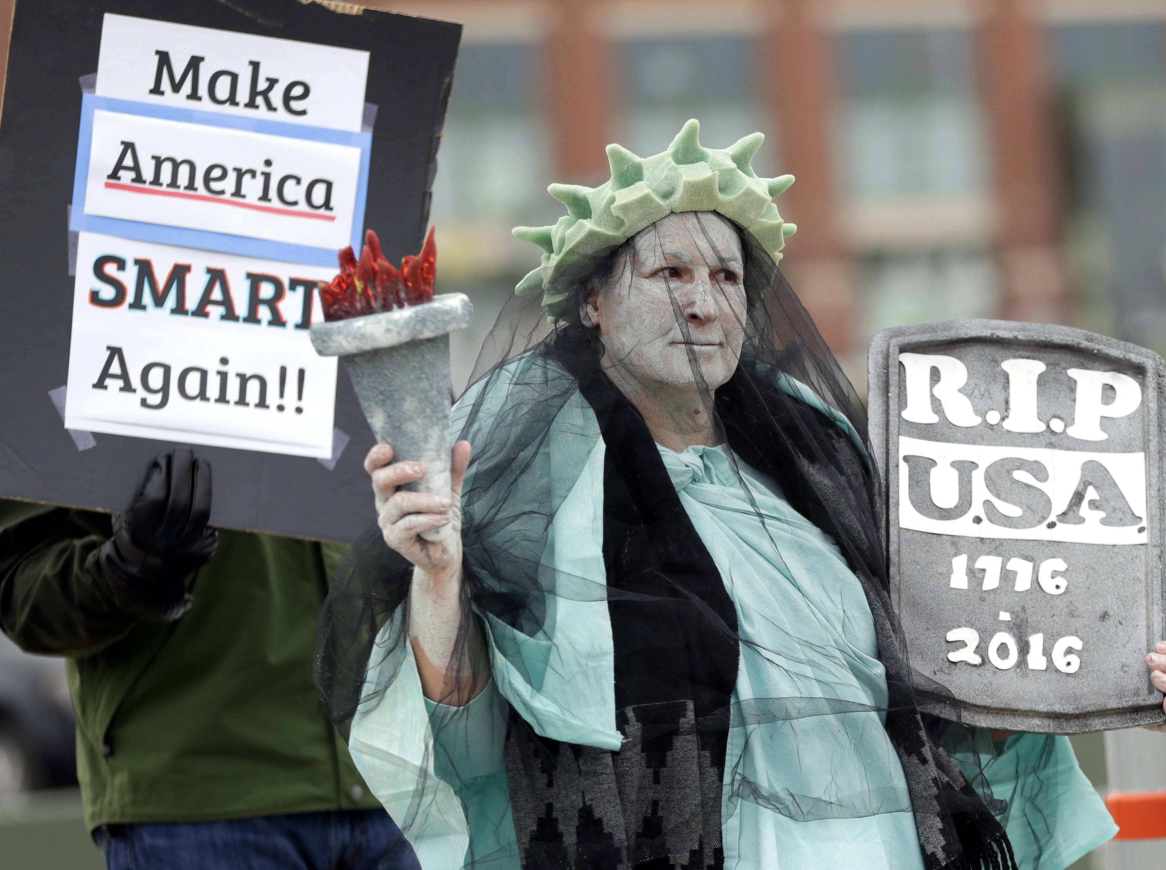 A woman dressed as the Statue of Liberty protests President Donald Trump before his rally at the Resch Center on April 27, 2019 in Ashwaubenon, Wis.