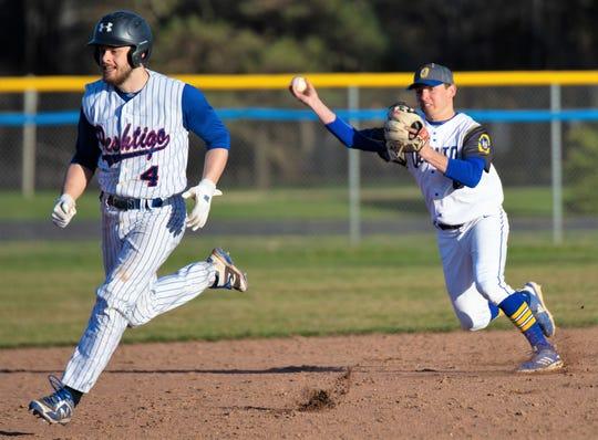 After fielding an infield hit, Oconto shortstop Bennett Frazer attempts to throw out a Peshtigo runner advancing to third base in a game April 26, 2019.