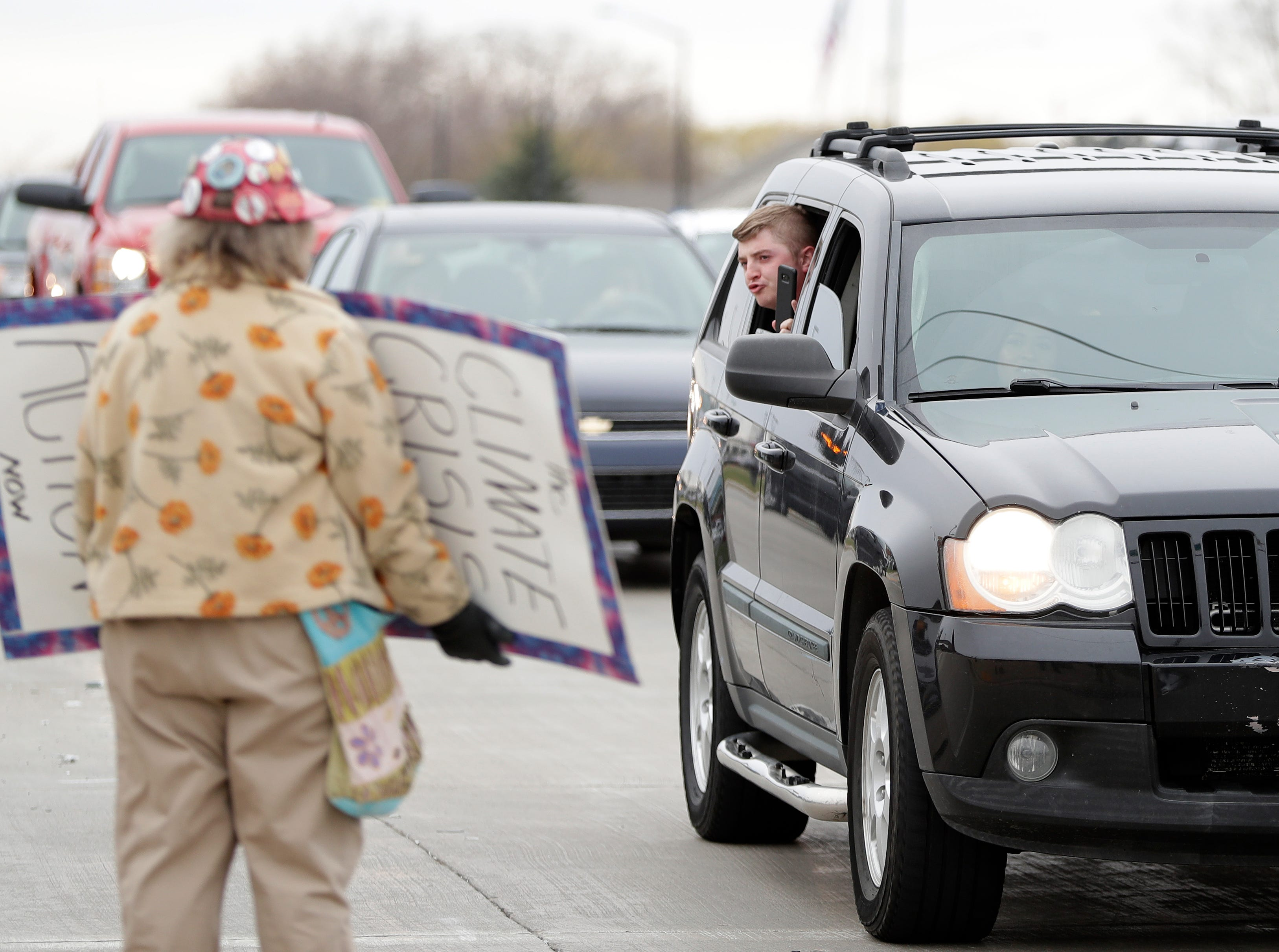 A man in a vehicle yells at President Donald Trump protesters on the corner of Ridge Road and Lombardi Avenue in Green Bay, Wis.