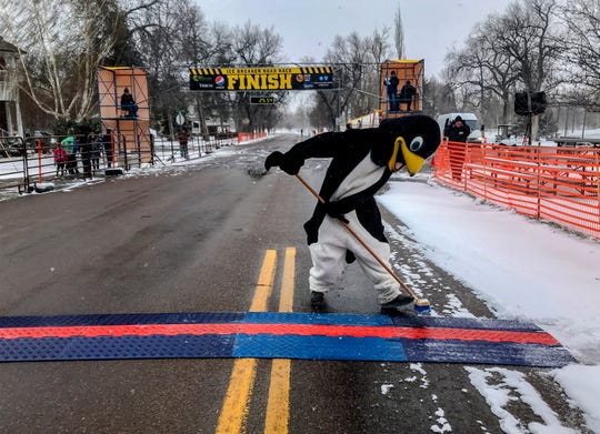 Pacer the penguin does some house keeping at the finish line of the Ice Breaker Road Race as snow continues to fall on Sunday afternoon.