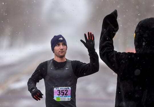 Adam Wollant of Bozeman high-fives Pacer the penguin as he crosses the finish line in first place during the Ice Breaker 5-mile run on Sunday afternoon.