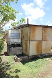 Dededo resident Peter Rosario, who holds a CHamoru Land Trust least for property without water and power infrastructure, fills a large white container each week so his family can bathe and flush the toilet in this shack on the property.