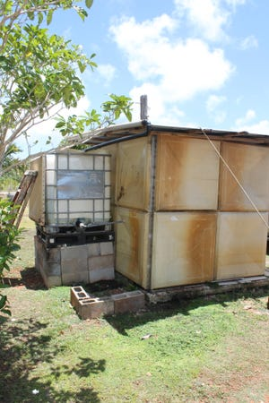 Dededo resident Peter Rosario, who holds a CHamoru Land Trust lease for property without water and power infrastructure, fills a large white container each week so his family can bathe and flush the toilet in this shack on the property. He has been hauling water in by truck for more than six years.