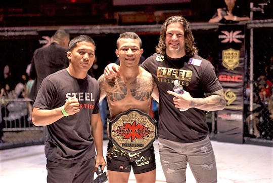 Ricky Camp, center, is all smiles after his 1st round TKO over Rodney Mondala to earn the bantamweight championship and belt. Camp's fight was the co-main event at X1 World Events #53, Champion 4 at the Blaisdell Arena in Hawaii on April 27.  His manager and training partner JJ Ambrose is pictured at right.