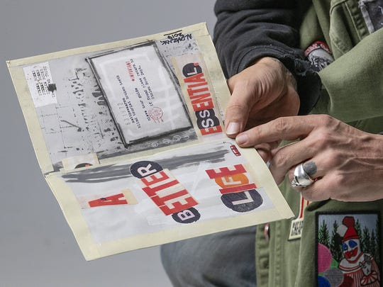 Matthew Aaron holds a homemade book that features his art and text contributions by New York City street artist Al Diaz.