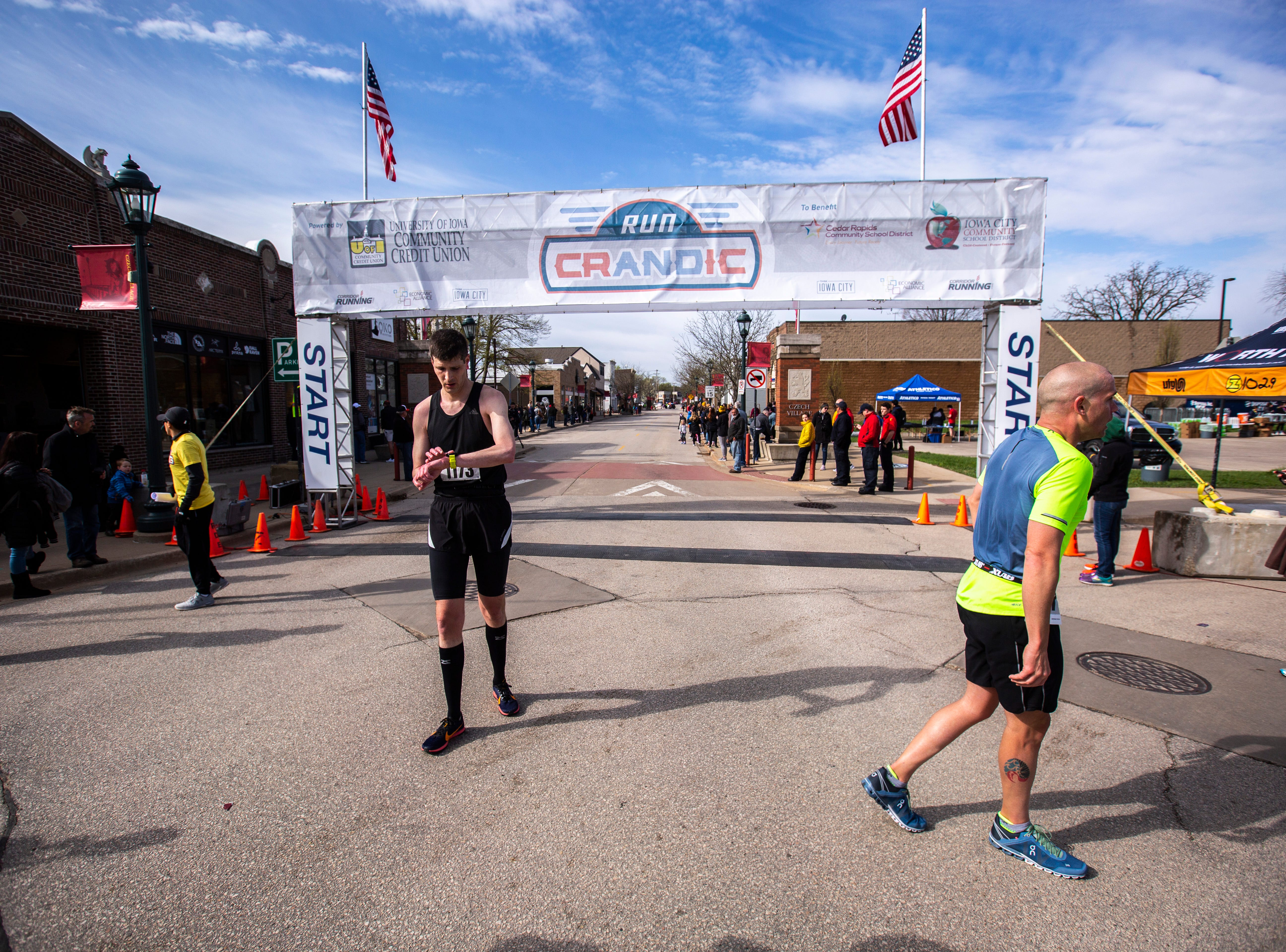 Sean McVeigh, left, checks his time after finishing with half marathon runners past the finish line during the second annual Run CRANDIC marathon, Sunday, April 28, 2019, along 16th Avenue SE in Cedar Rapids, Iowa.