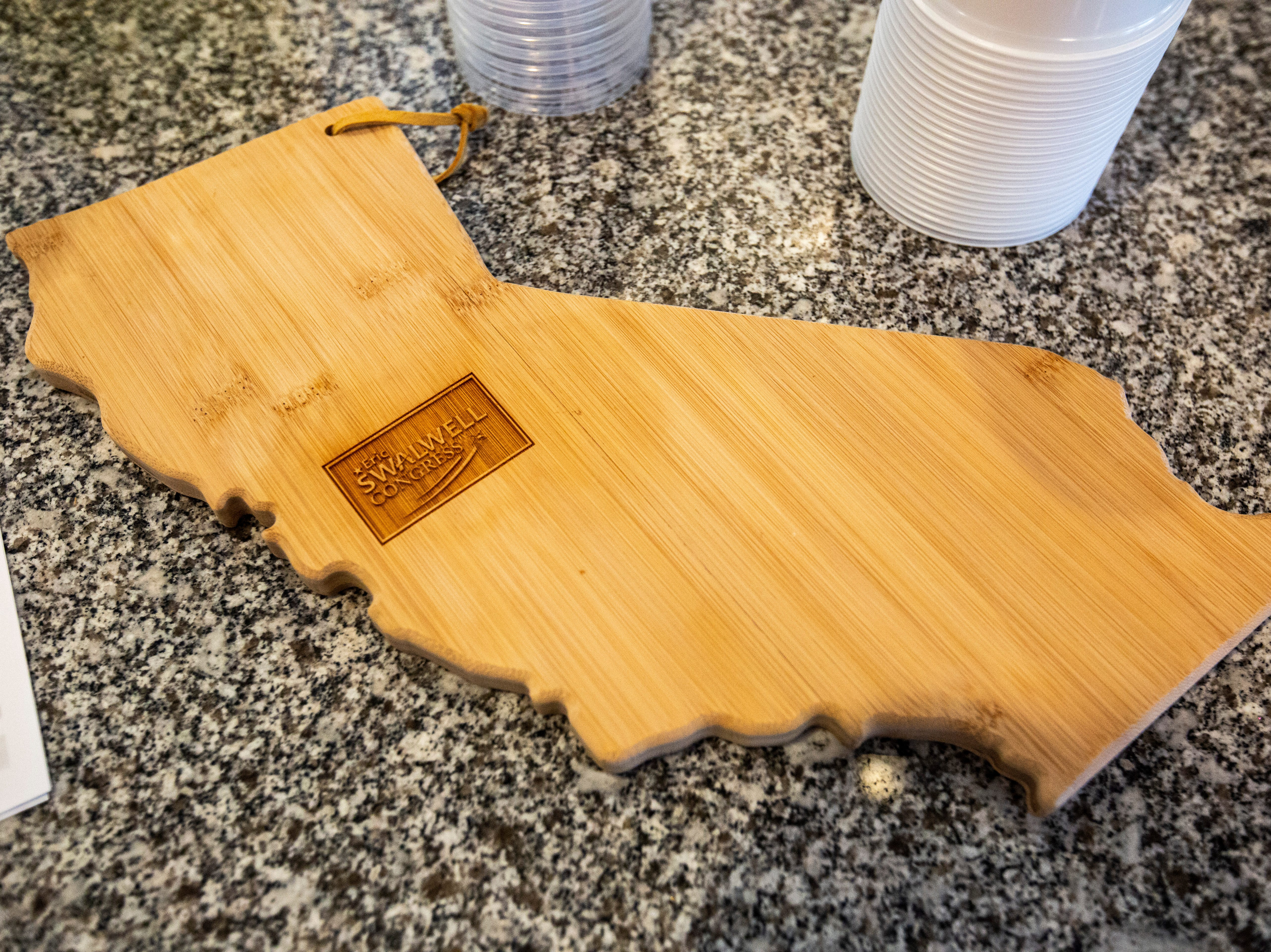 """A wooden cutting board in the shape of California for U.S. Rep. Eric Swalwell, D-Calif., is seen while he speaks to a group at a house party hosted by the """"Potluck Insurgency"""" group, Sunday, April 28, 2019, at a home in North Liberty, Iowa."""