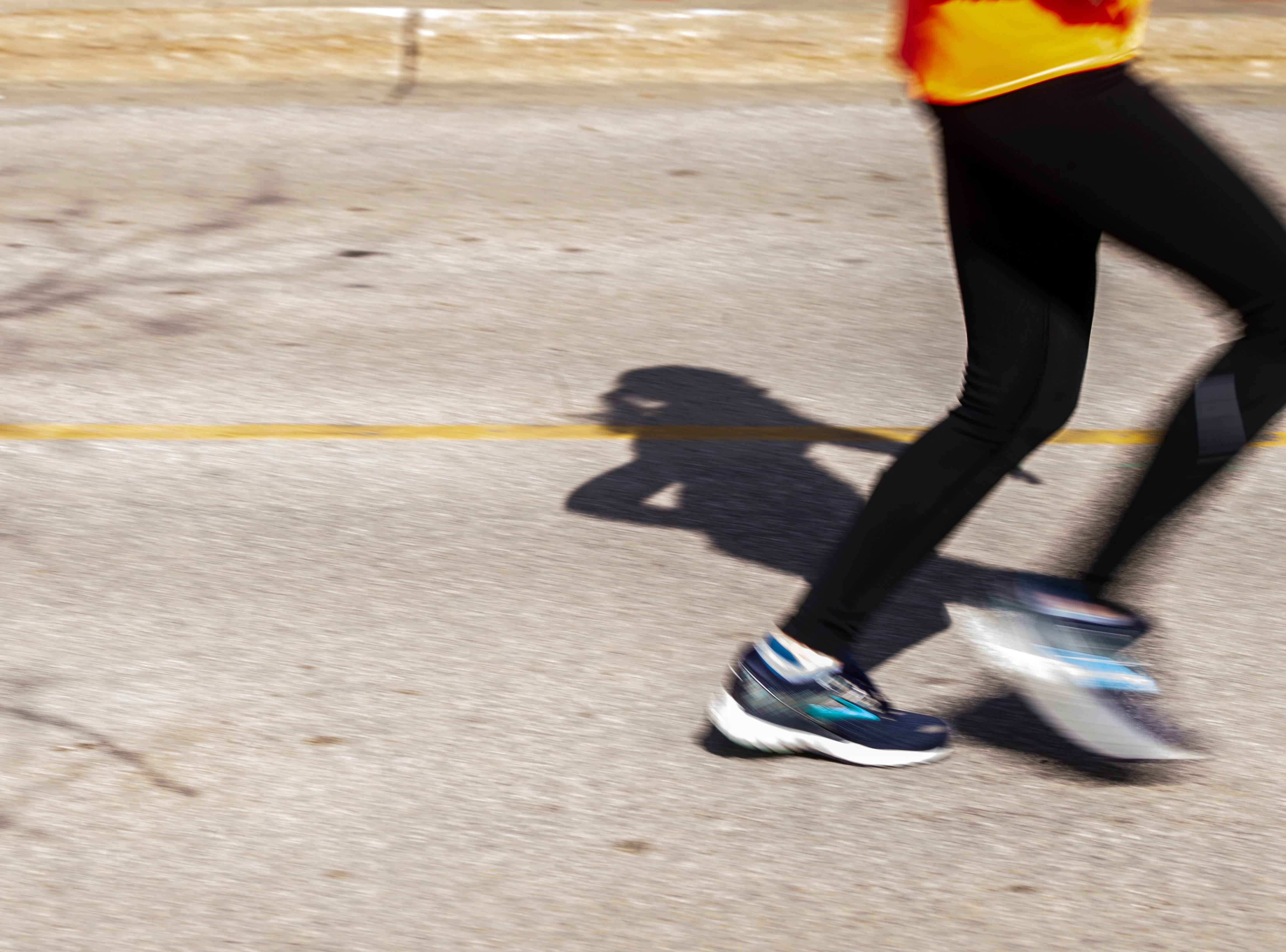 A shadow is seen as a runner nears the finish line on the pavement during the second annual Run CRANDIC marathon, Sunday, April 28, 2019, along 16th Avenue SE in Cedar Rapids, Iowa.